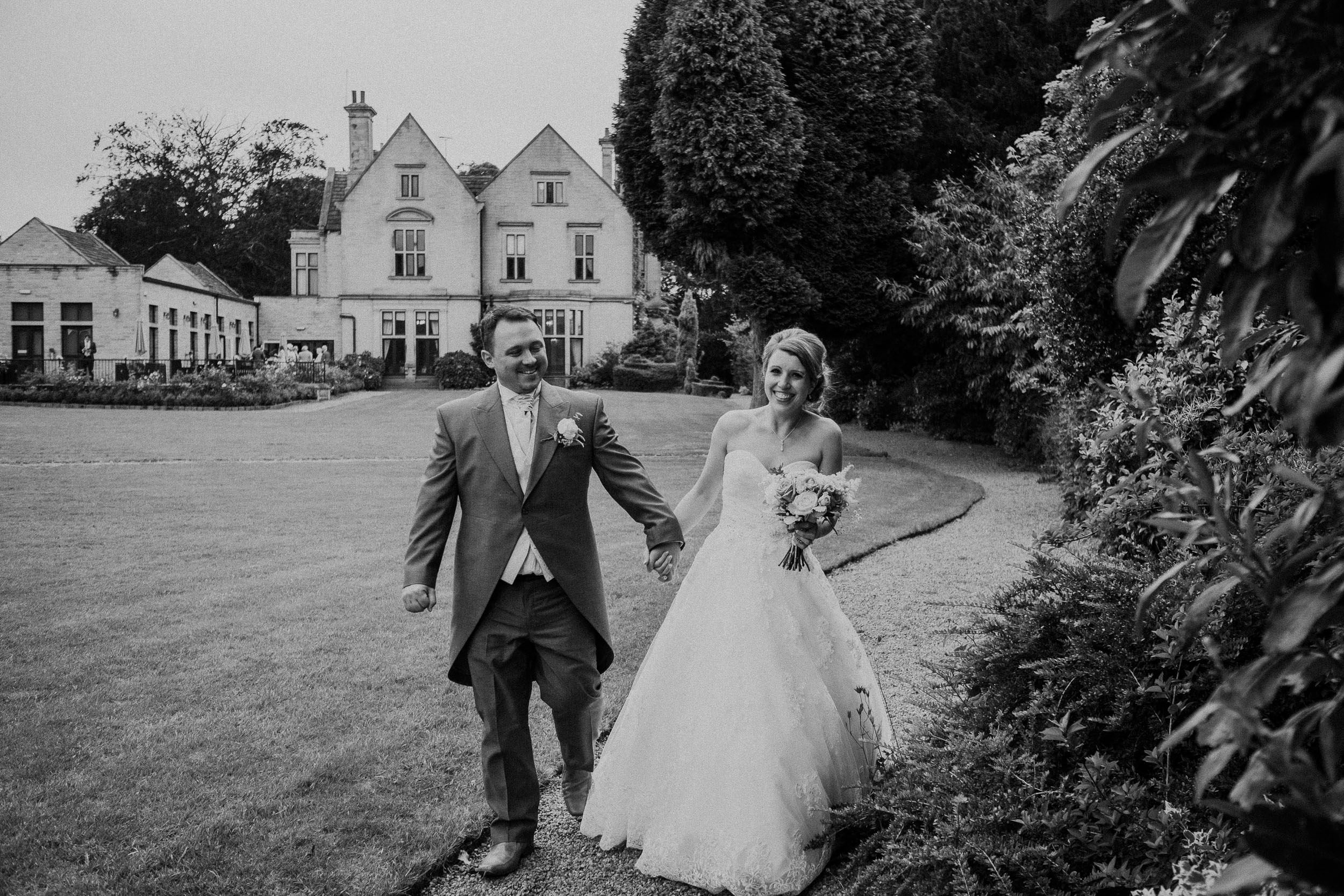 Black and white photo of bride and groom walking through grounds of Blagden Hall