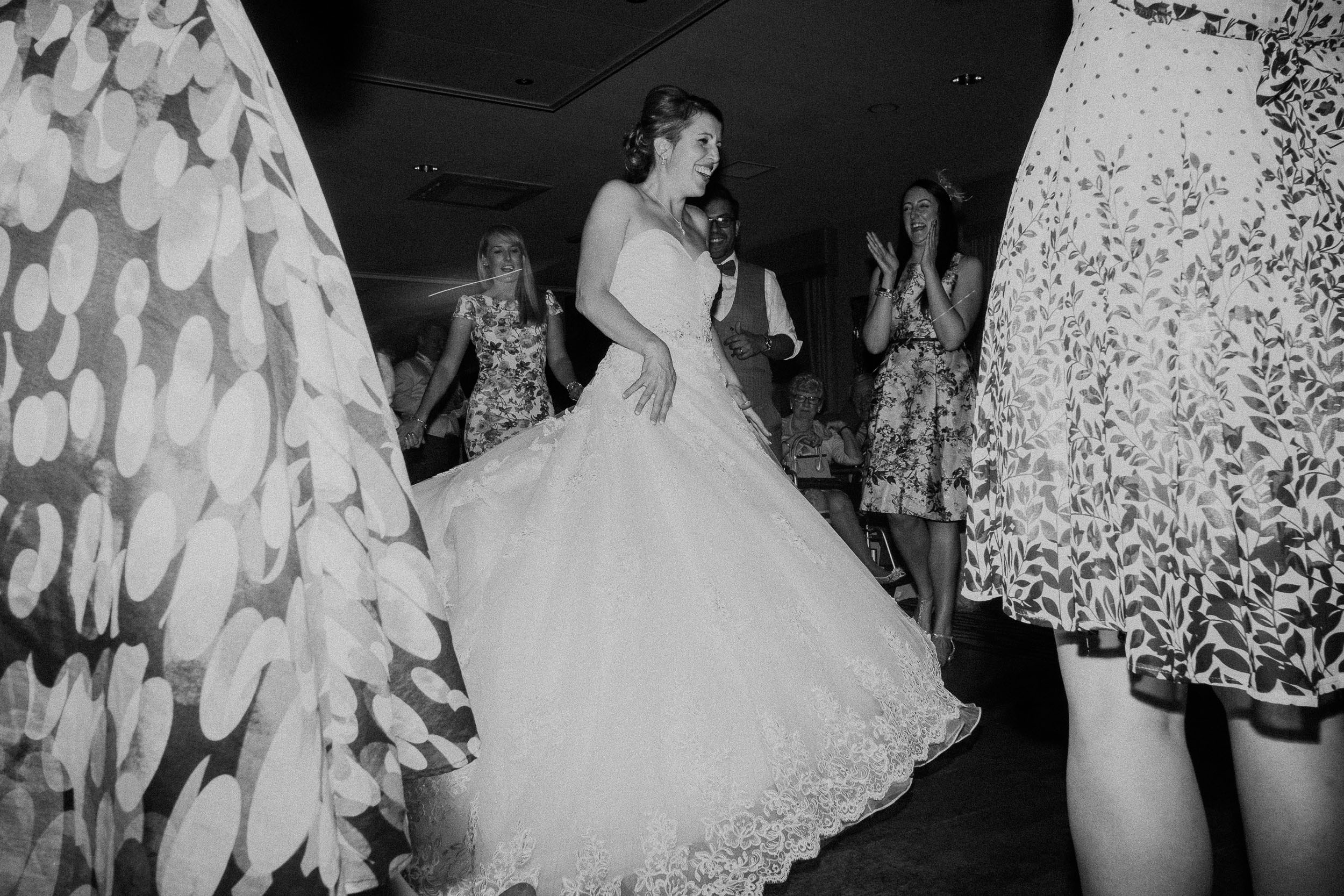 Black and white photo of bride dancing and laughing