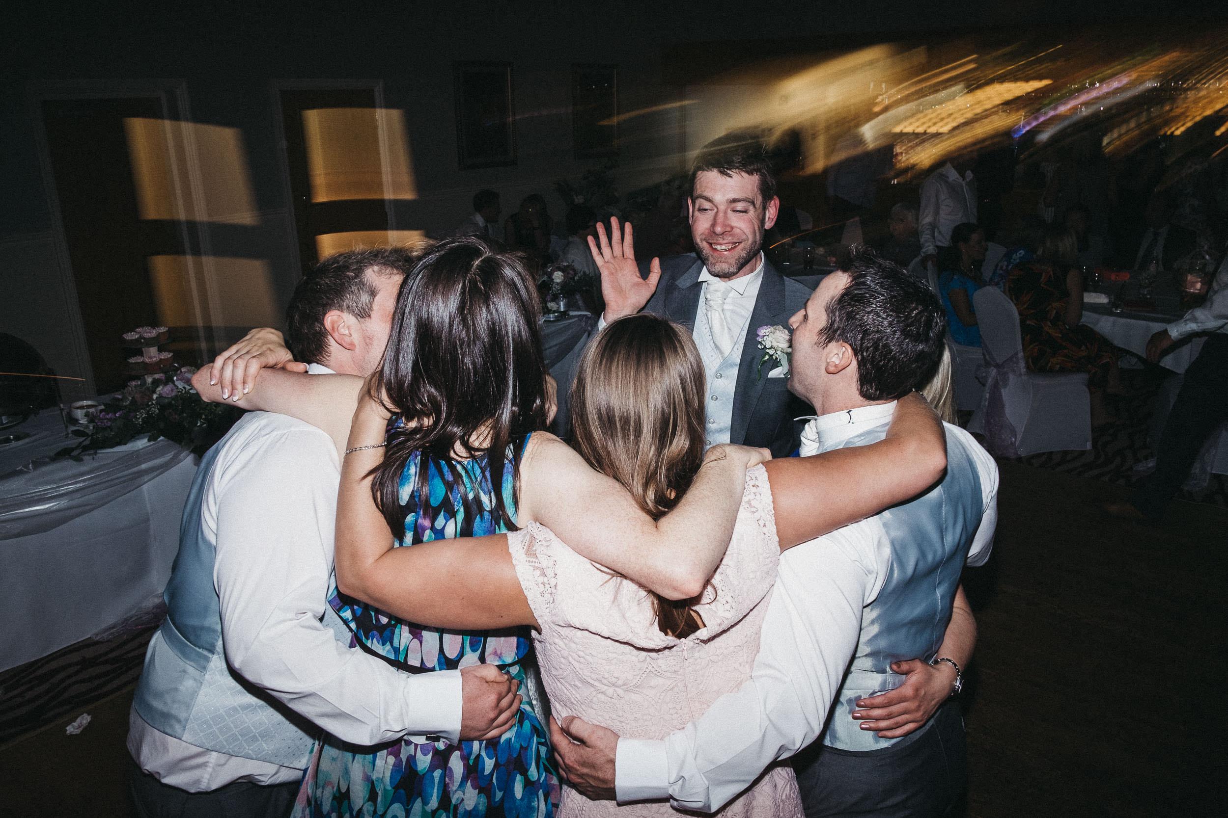 Groomsman squeezes into group hug on dance floor