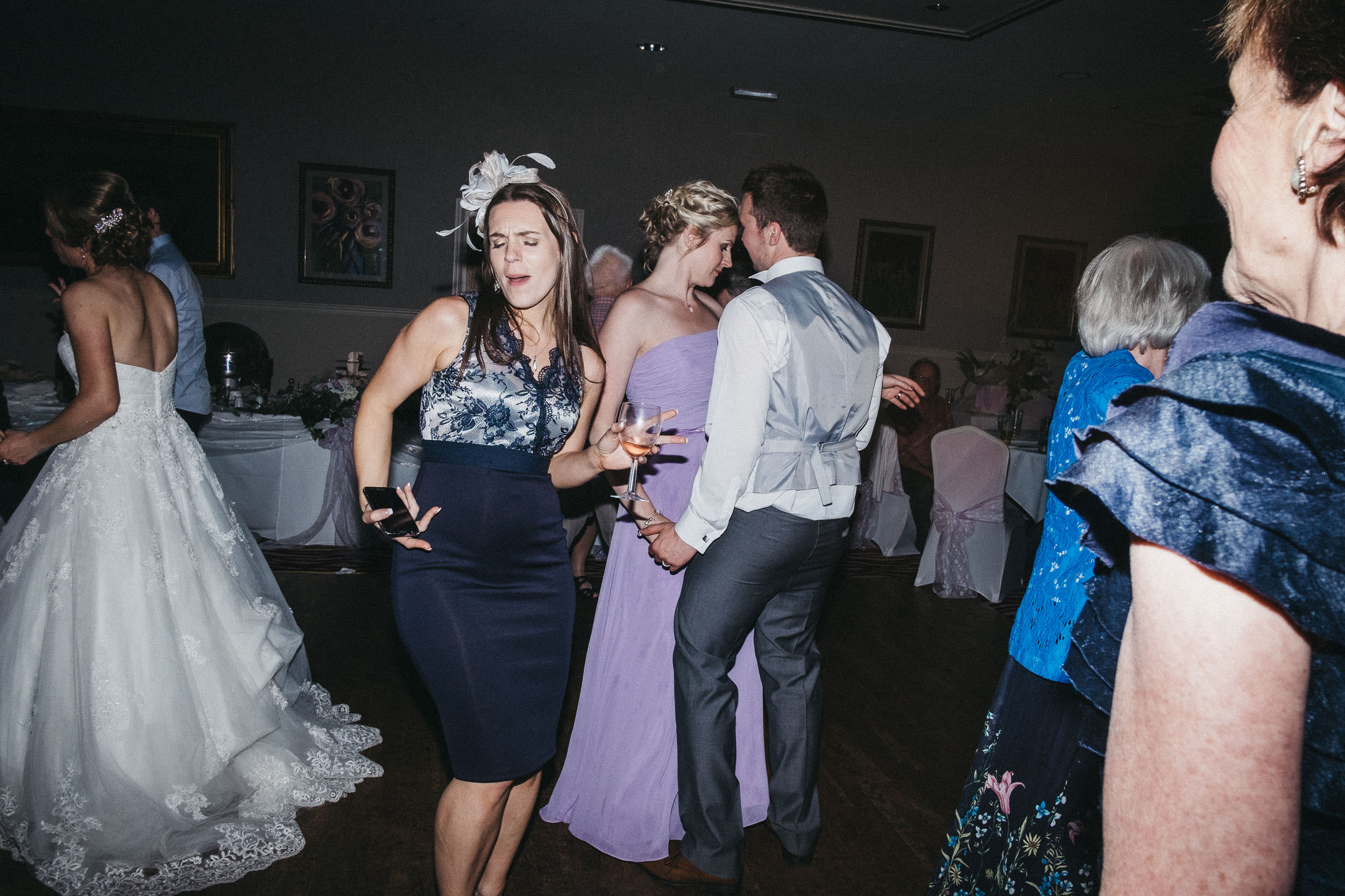 Quirky photo of wedding guests dancing awkwardly