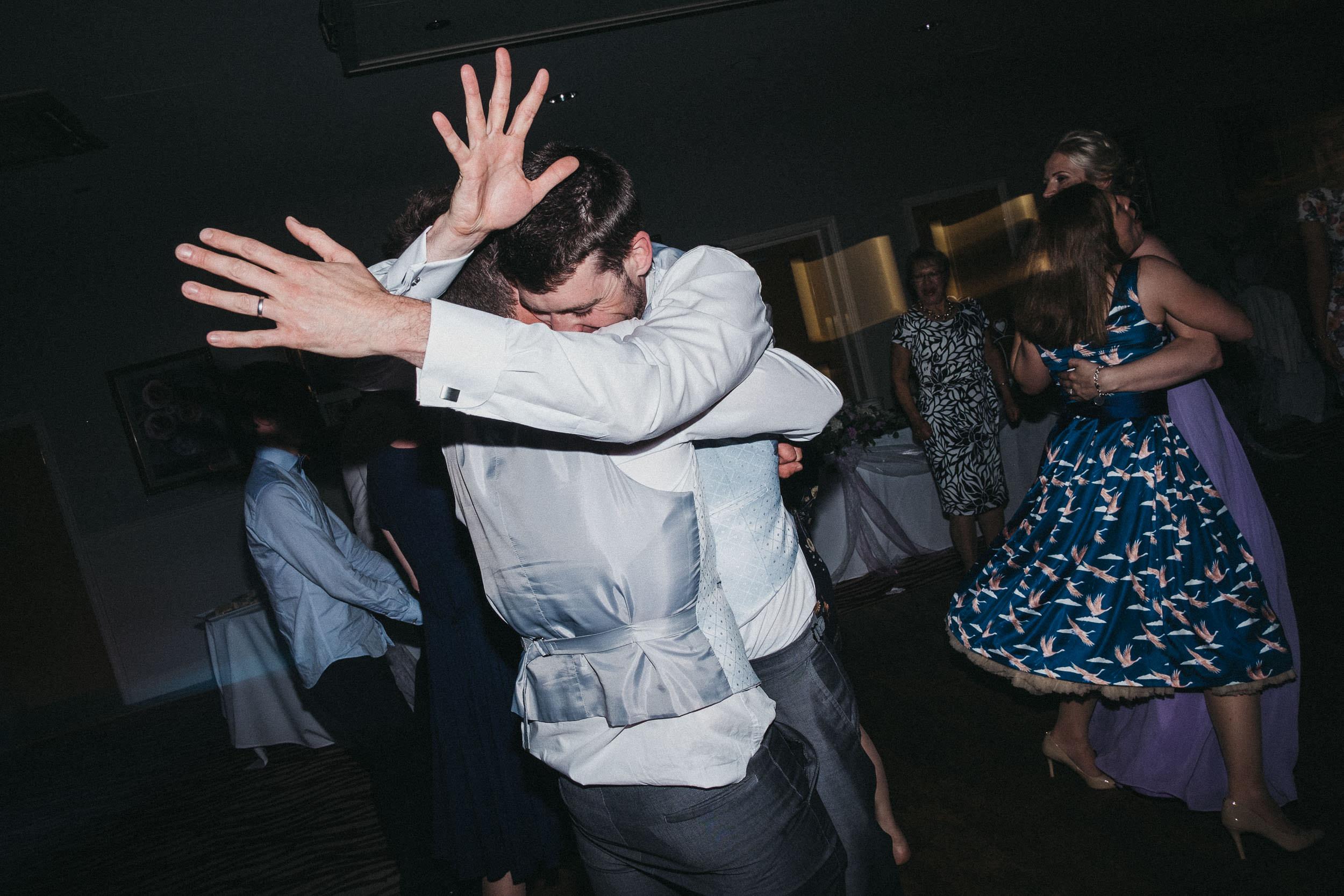 Groomsman throws his arms around another groomsman