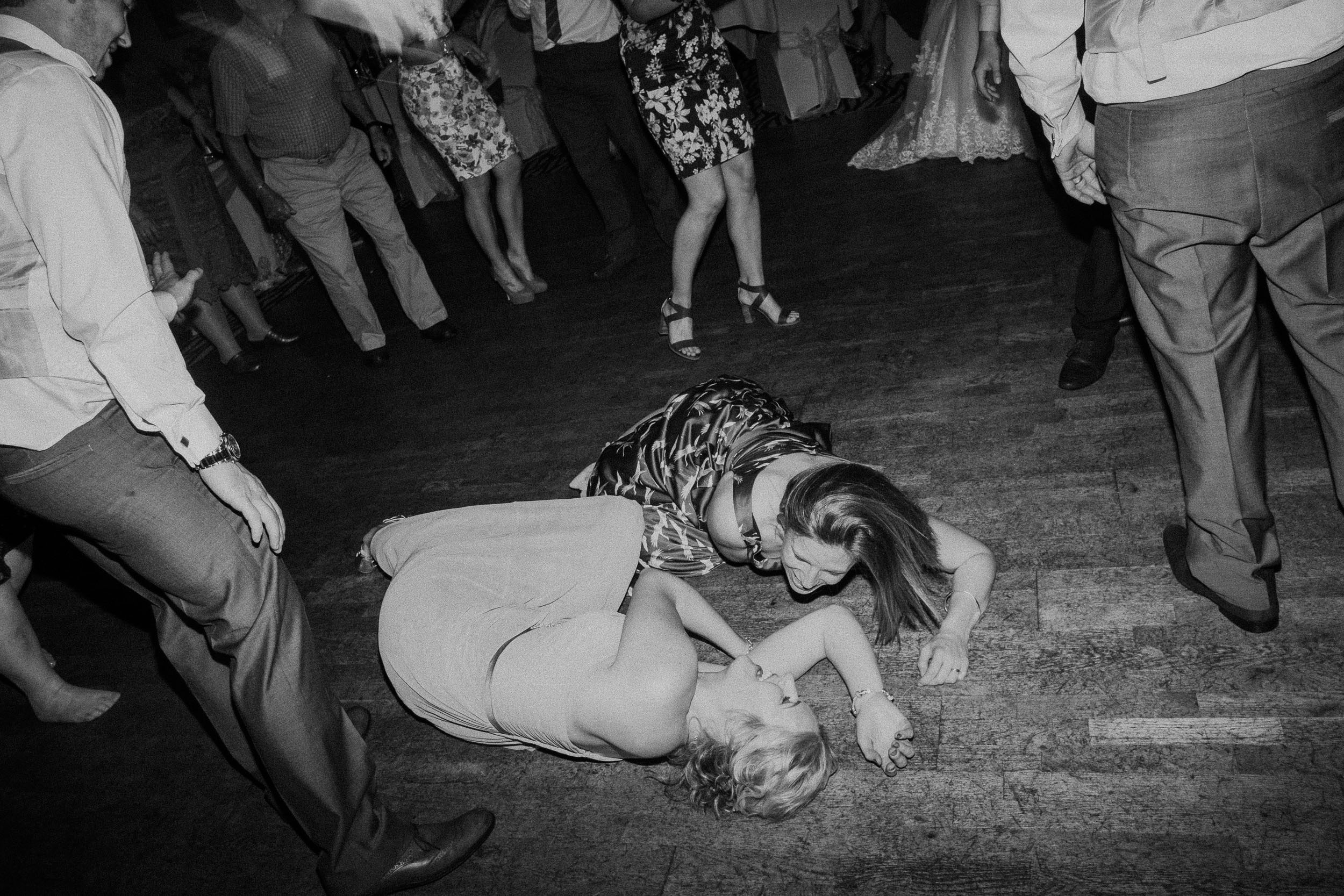 Black and white photo of bridesmaids falling onto dance floor