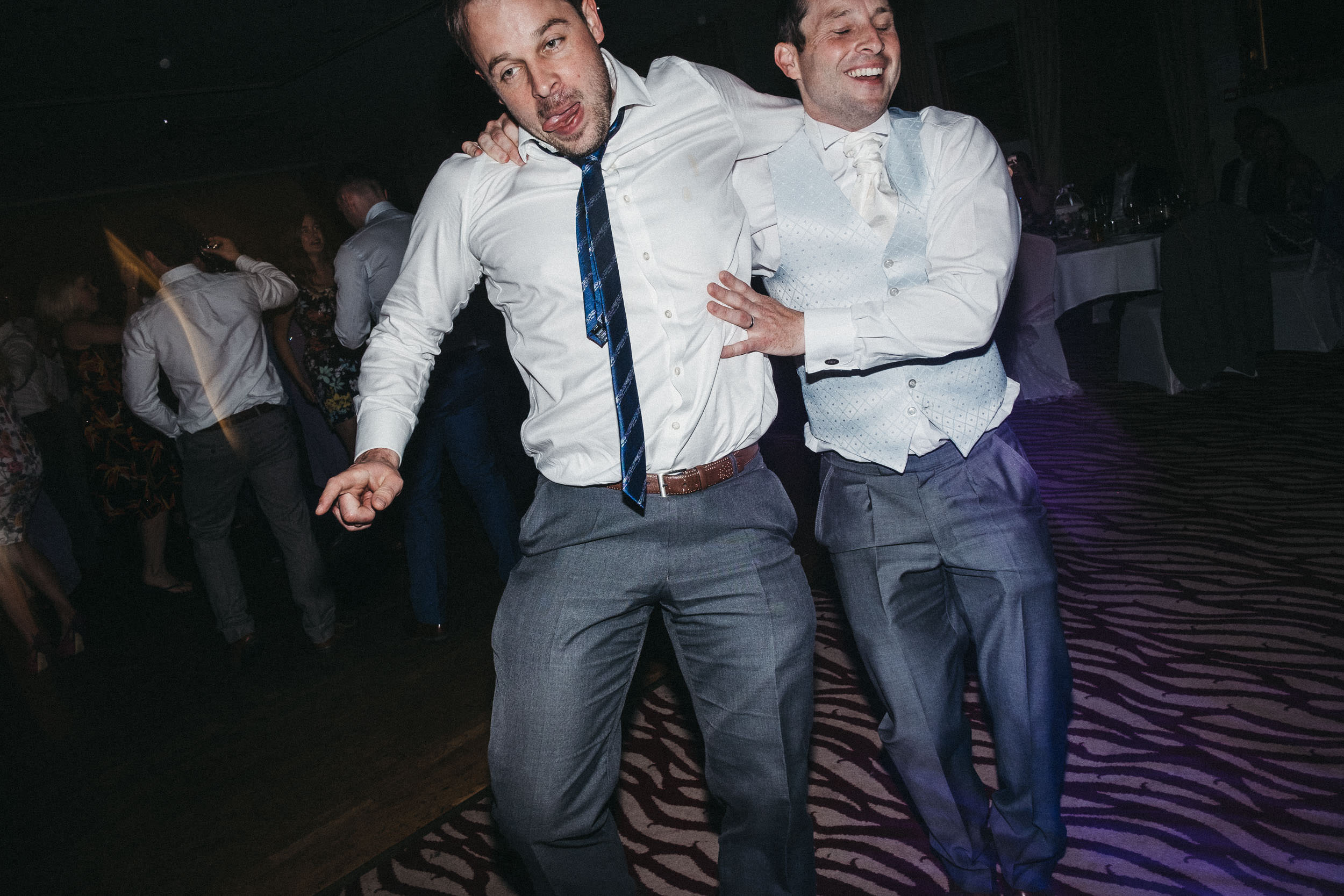 Drunk groomsmen pull funny faces while dancing