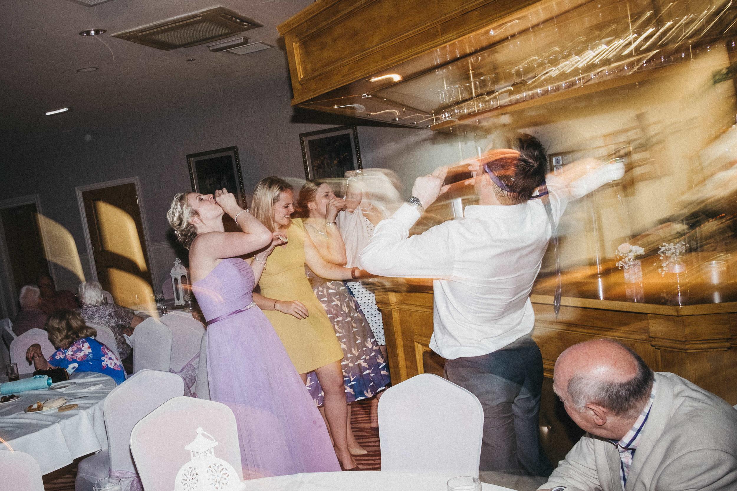 Blurry photo f bridesmaids doing shots at bar