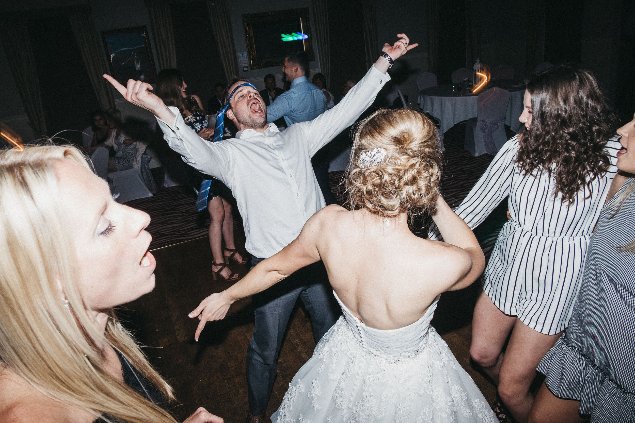 Groomsman singing on dance floor with tie tied around his head