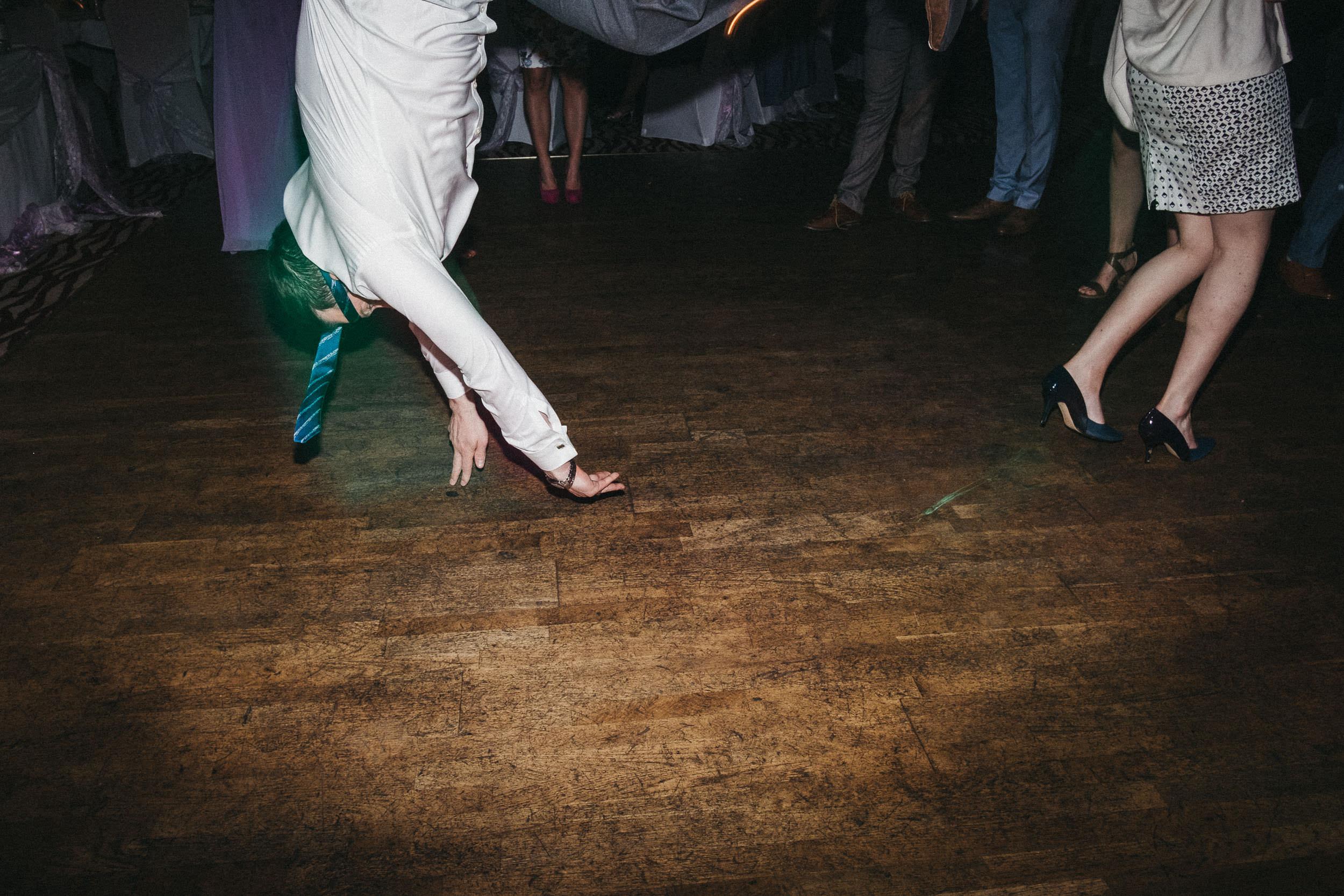 Groomsman somersaulting through air on wedding dance floor