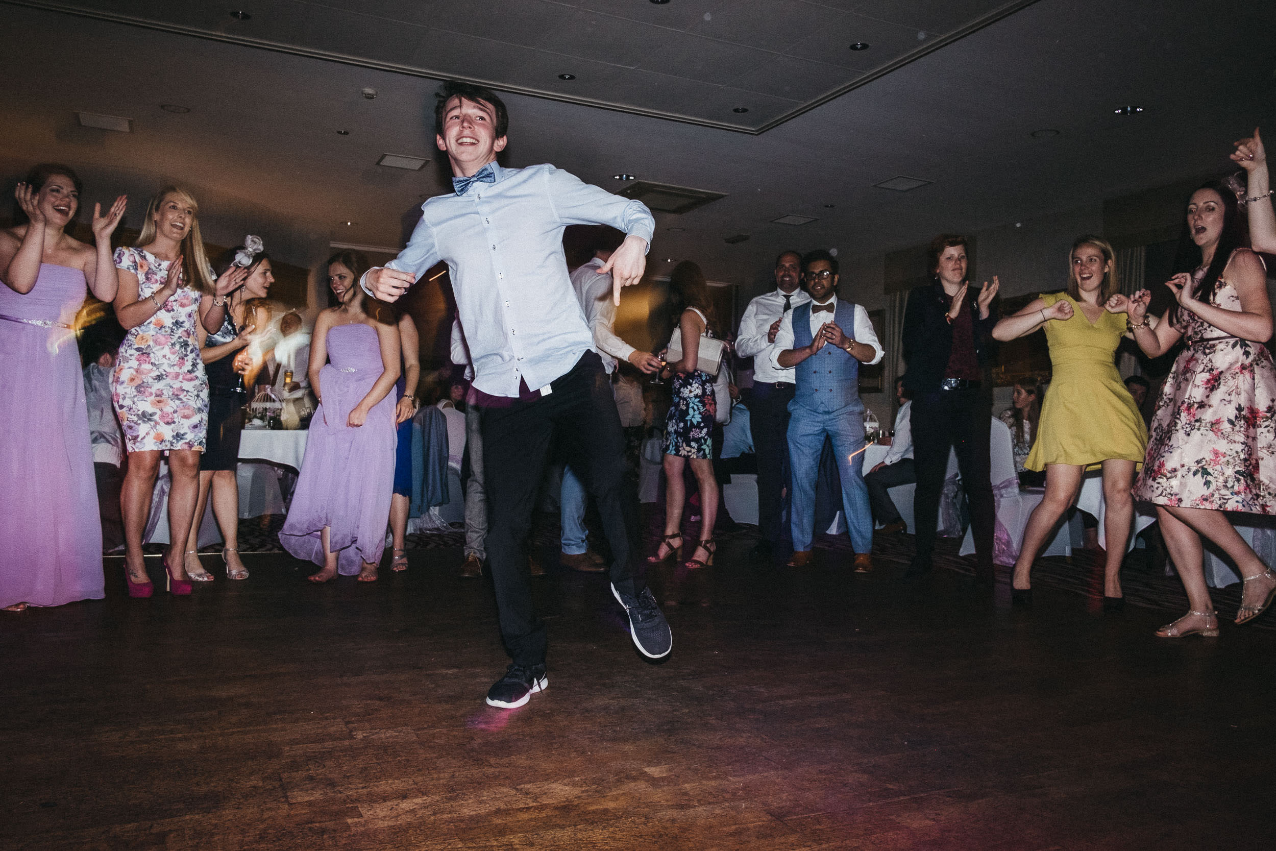 Young wedding guest dancing while other guest watch