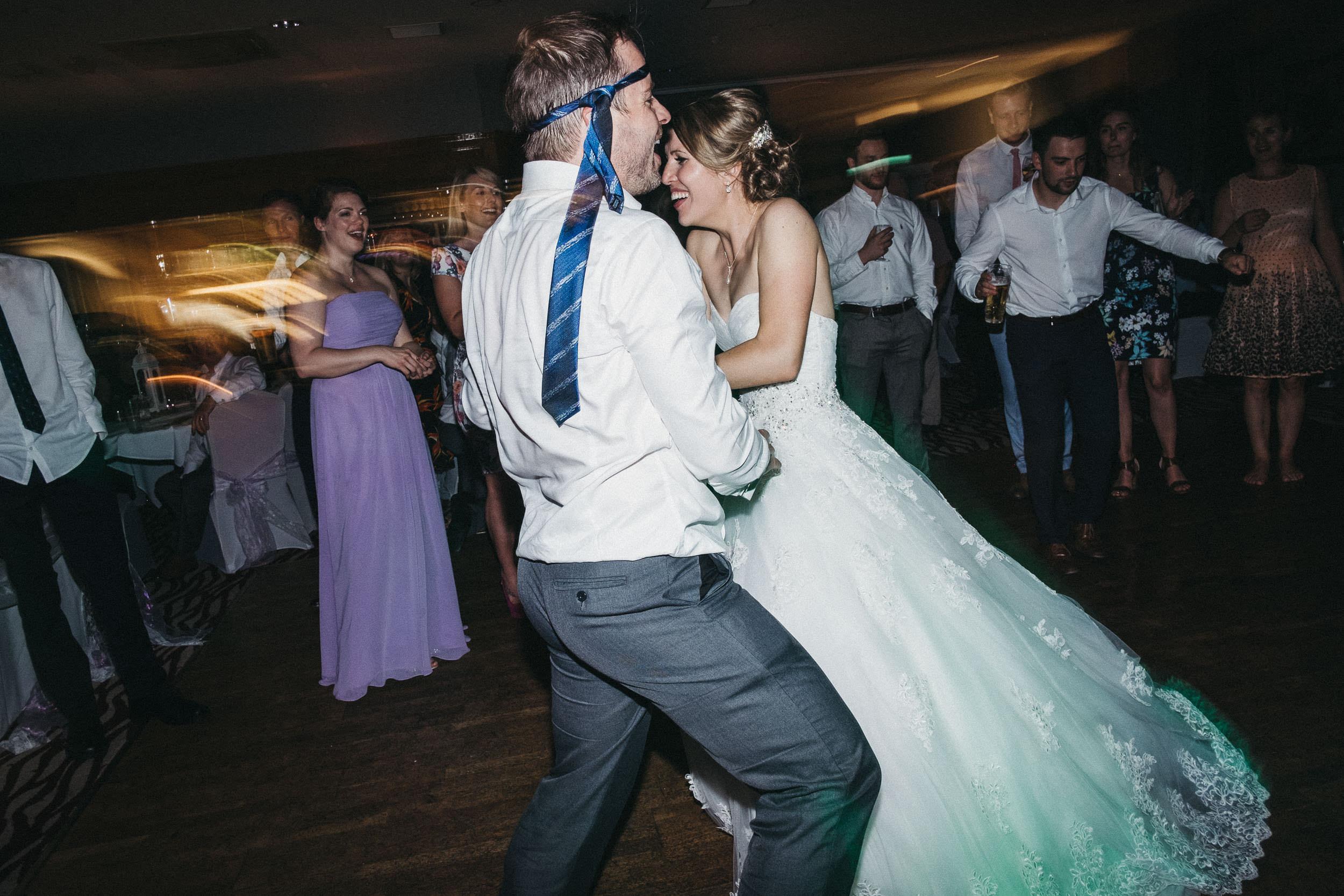 Groomsman dances with bride with tie tied around his head