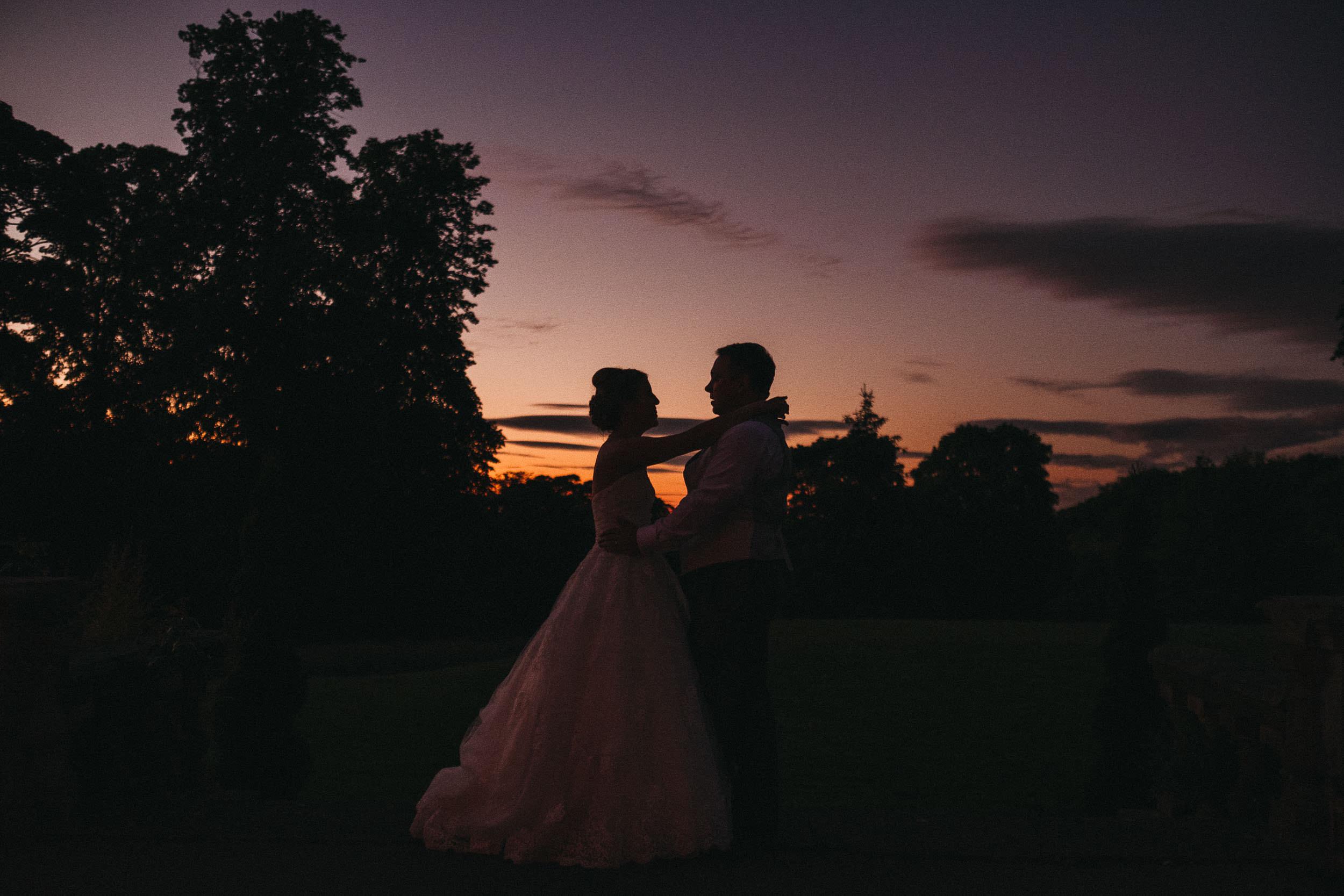 Bride and groom hug at sunset at Bagden Hall