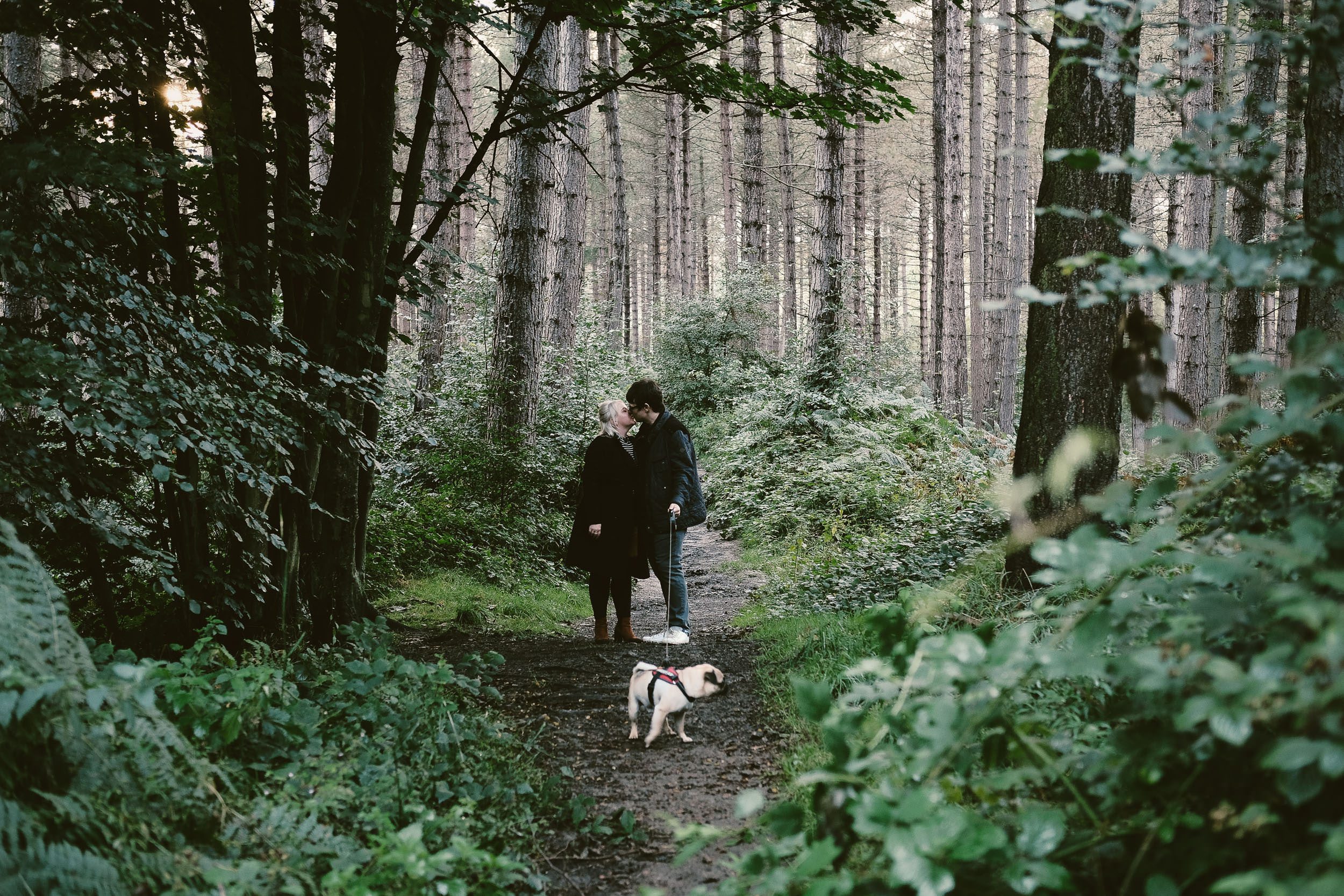 Engaged couple kiss on muddy forest trail while walking dog