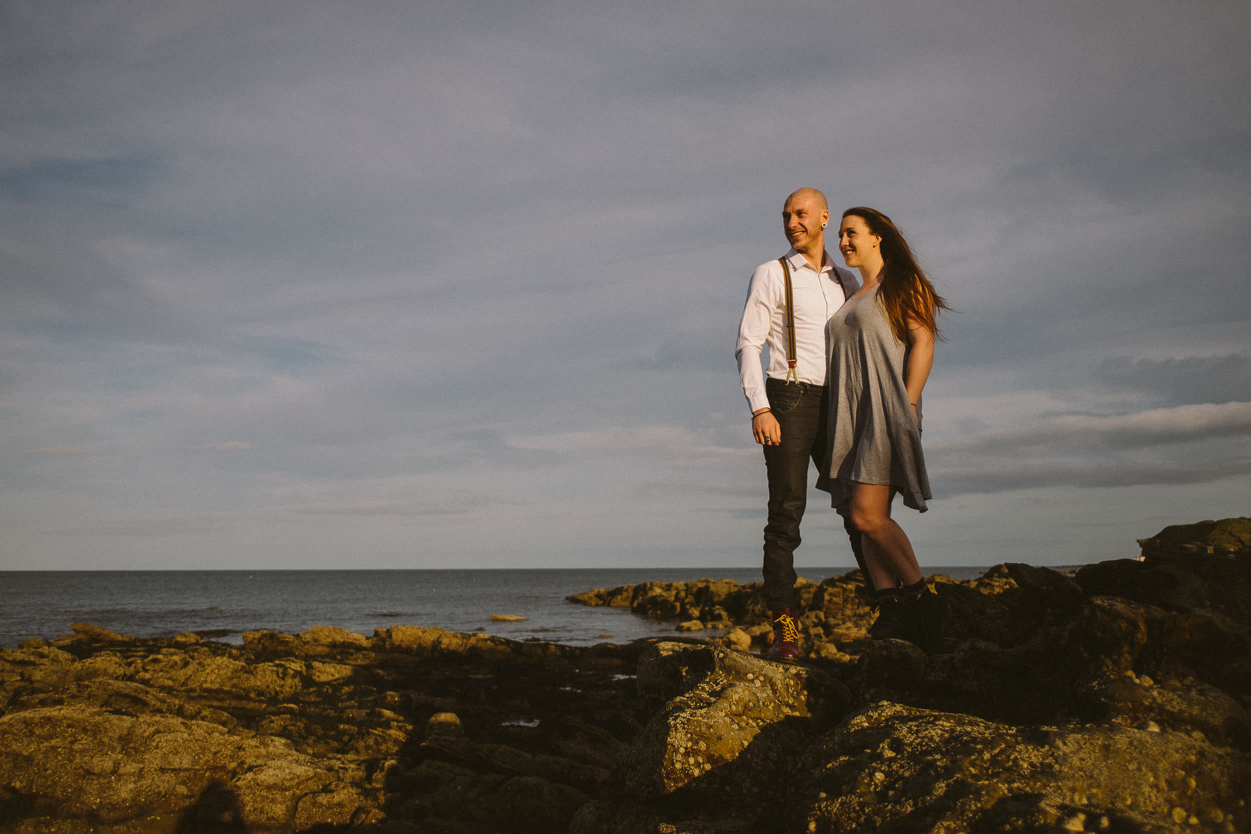 Couple smiling while standing on rock in sea in warm sunlight