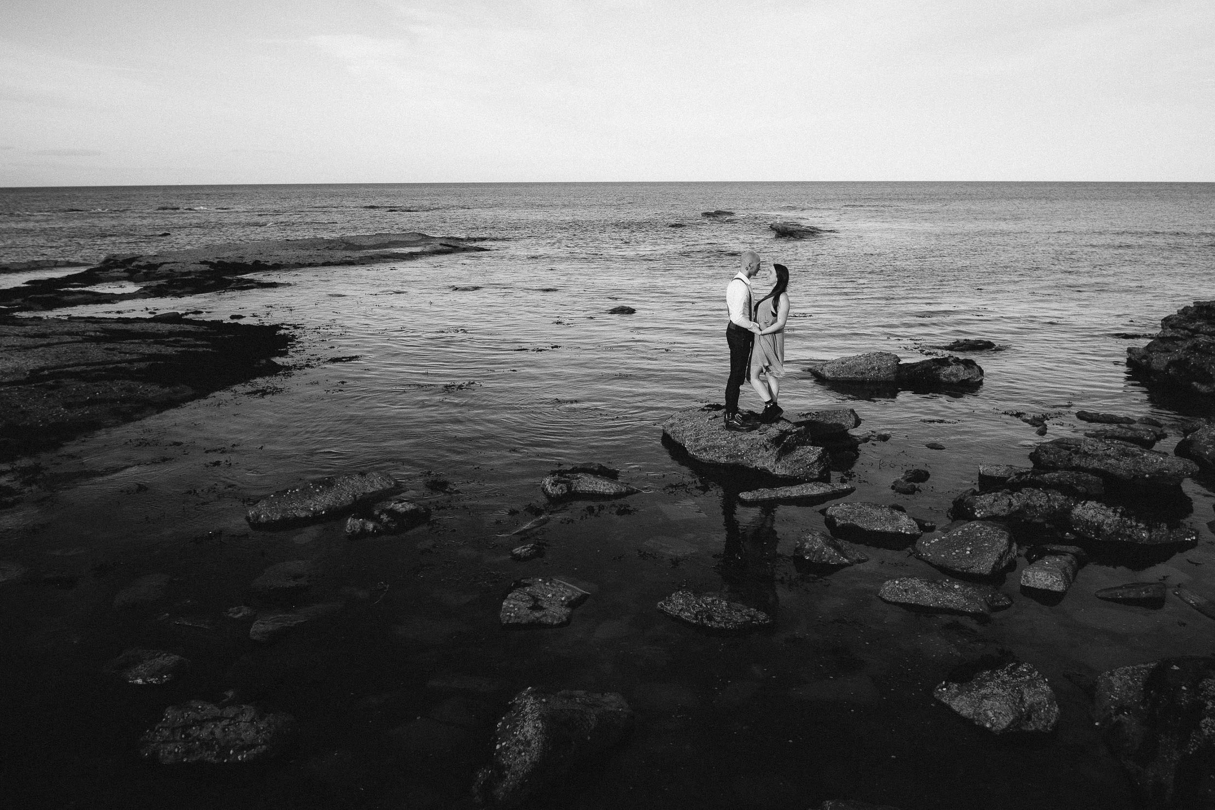 Back and white photo of couple standing on rock with sea in background
