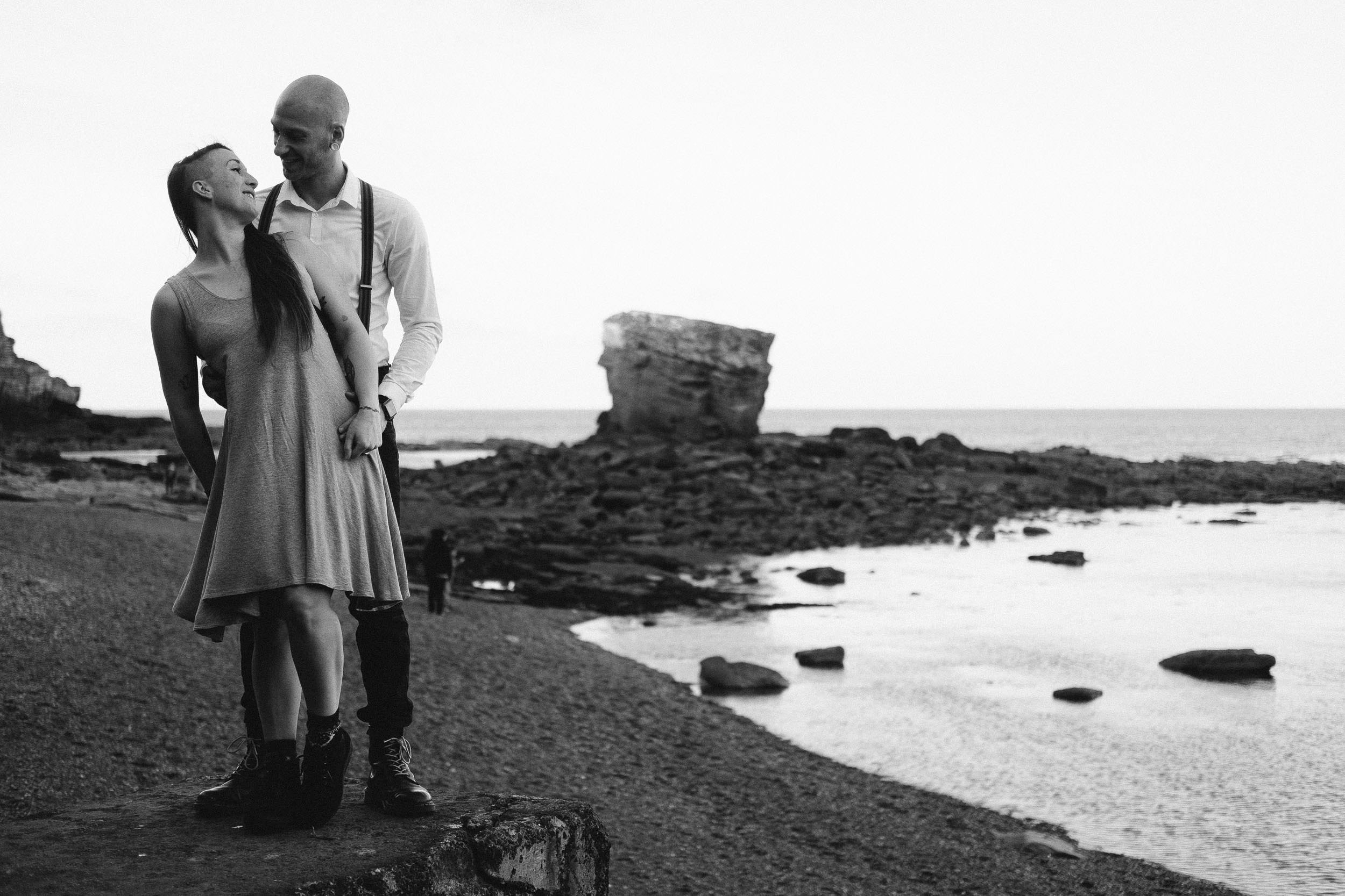 Back and white photo of couple at Seaton Sluice with Rocky Island behind