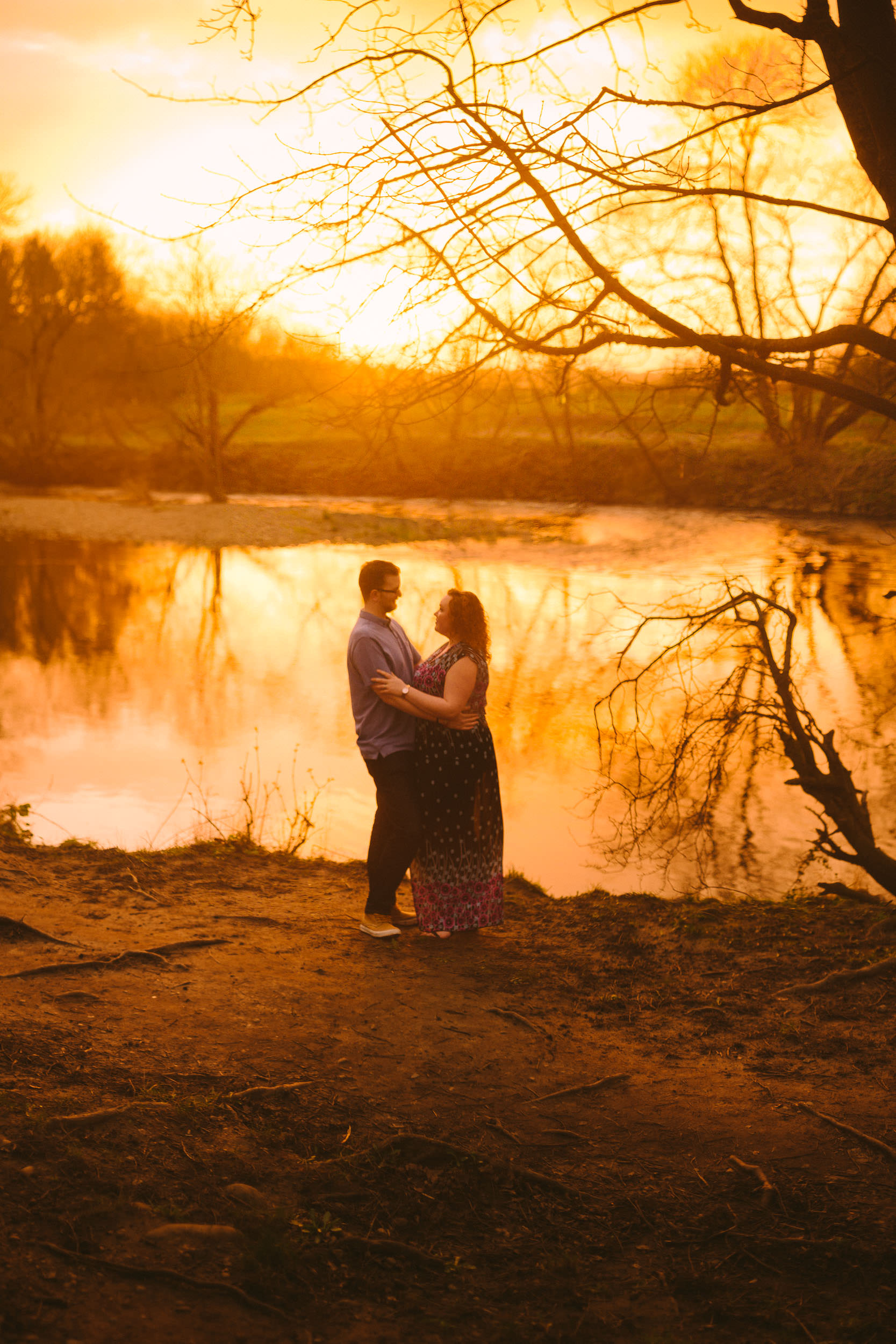A Brenizer method photo of a couple looking into each others eyes while standing by a river in golden sunlight