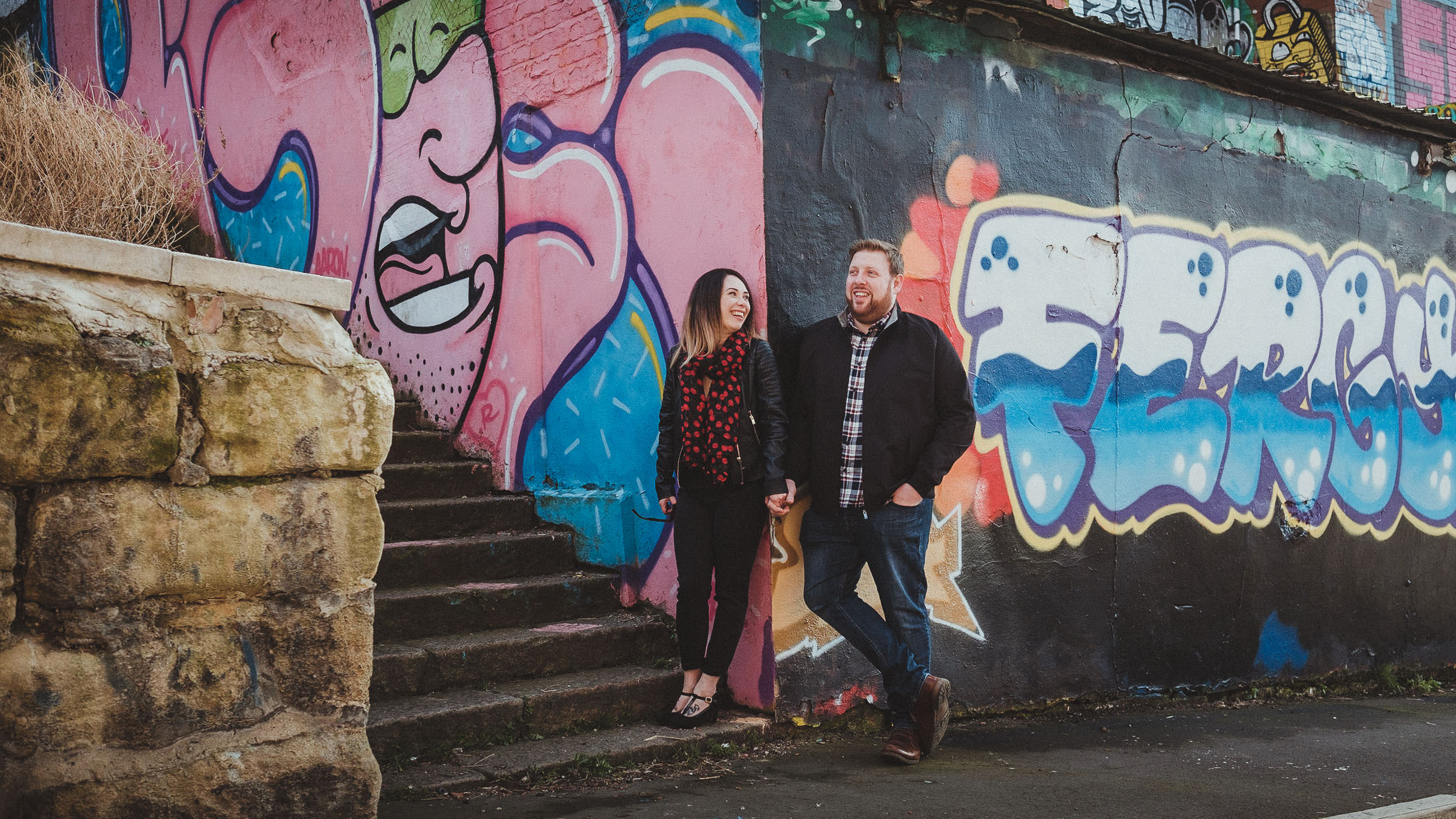 A couple hold hands while standing on a graffiti covered street corner in the Ouseburn