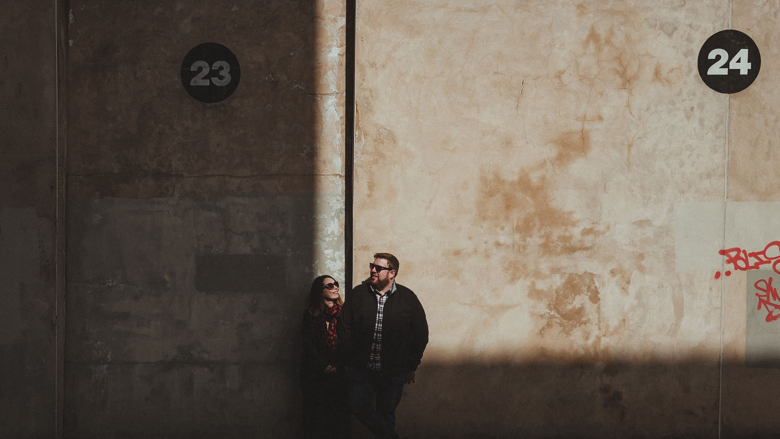 A couple standing in front of a large textured wall with deep shadows all around