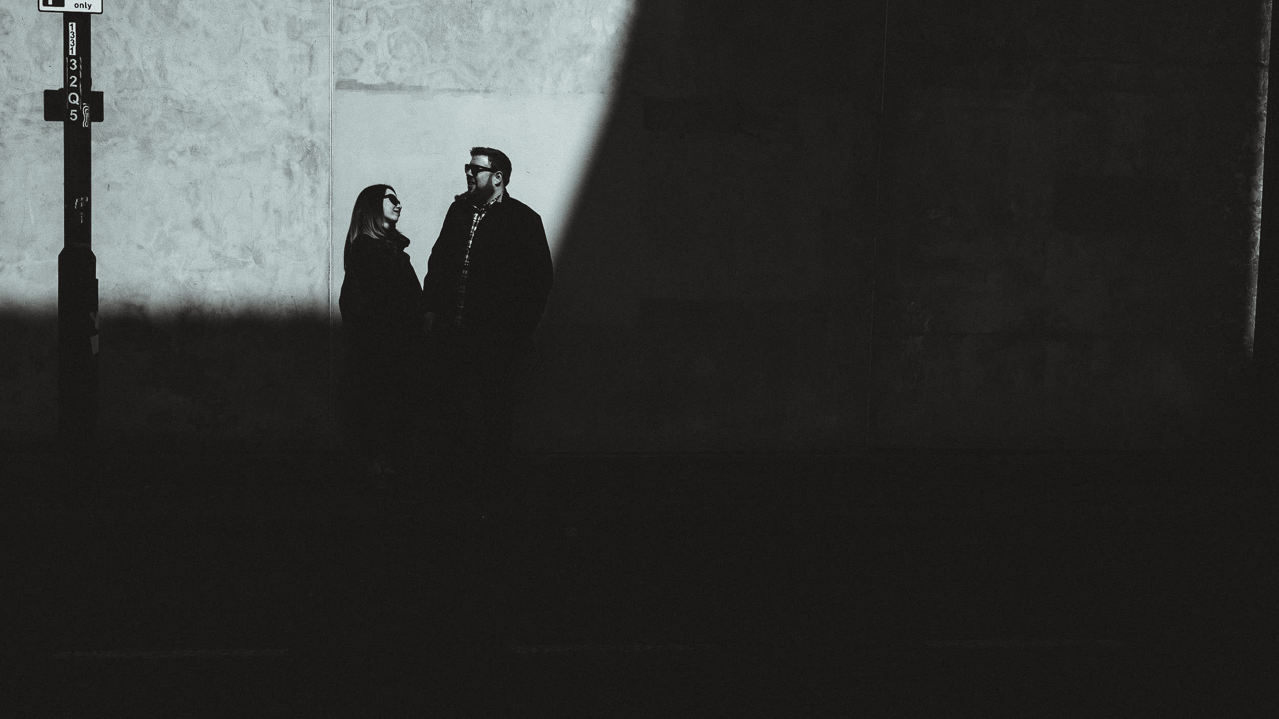 A black and white photo of a couple on Newcastle Quayside partly obscured by a large shadow