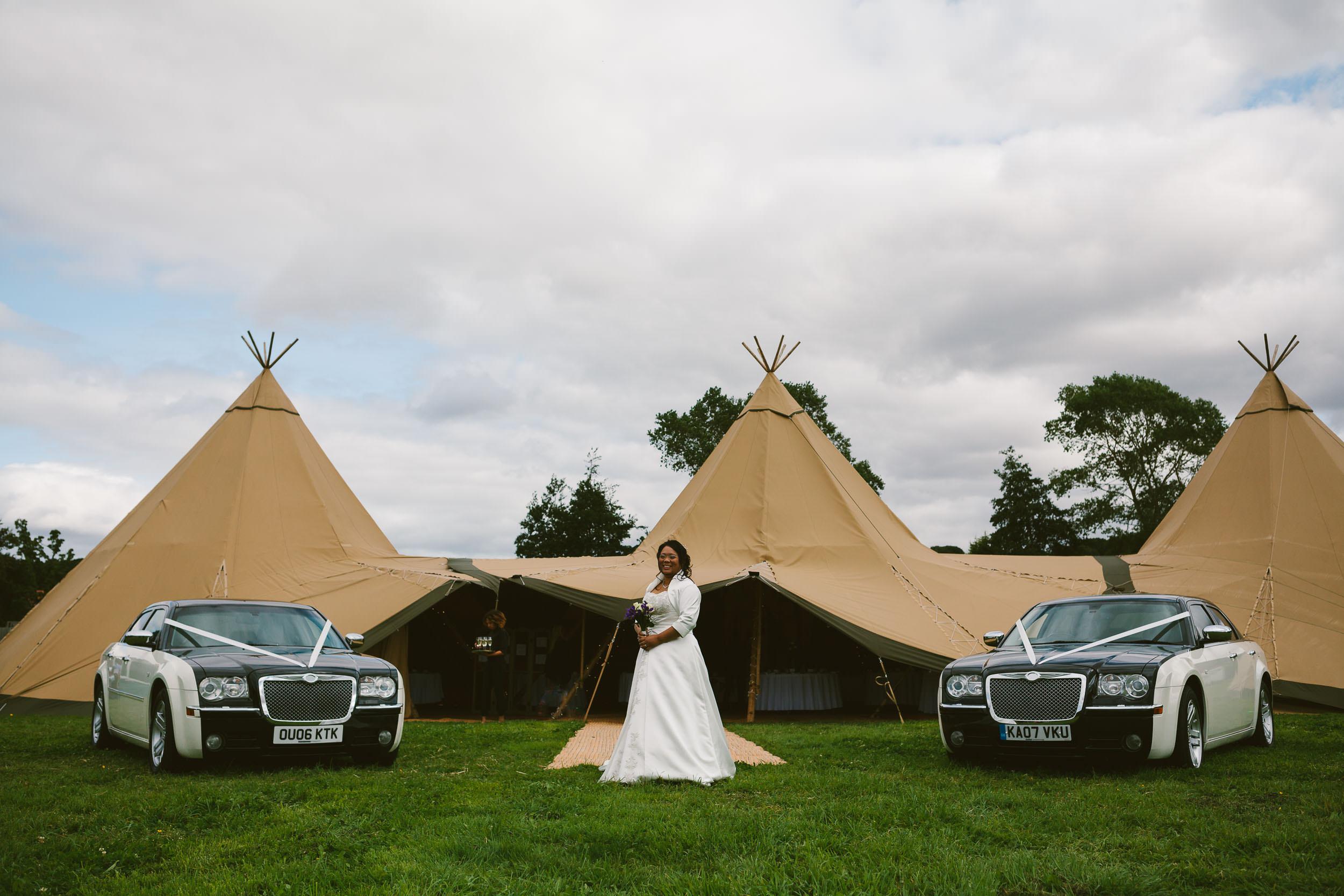Bride poses between two Bentleys with Tipi in background