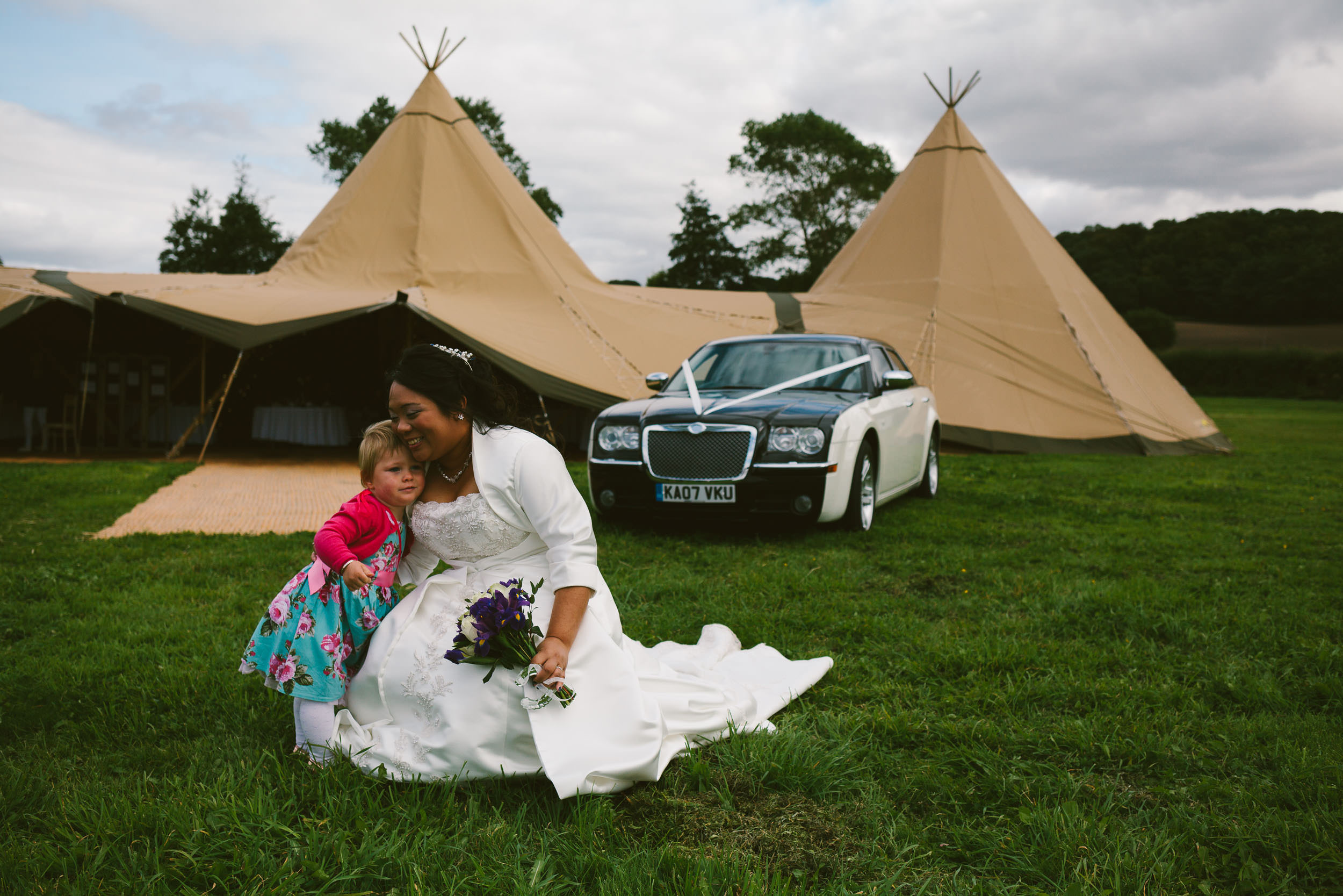 Bride cuddles daughter with tipi and wedding car in background