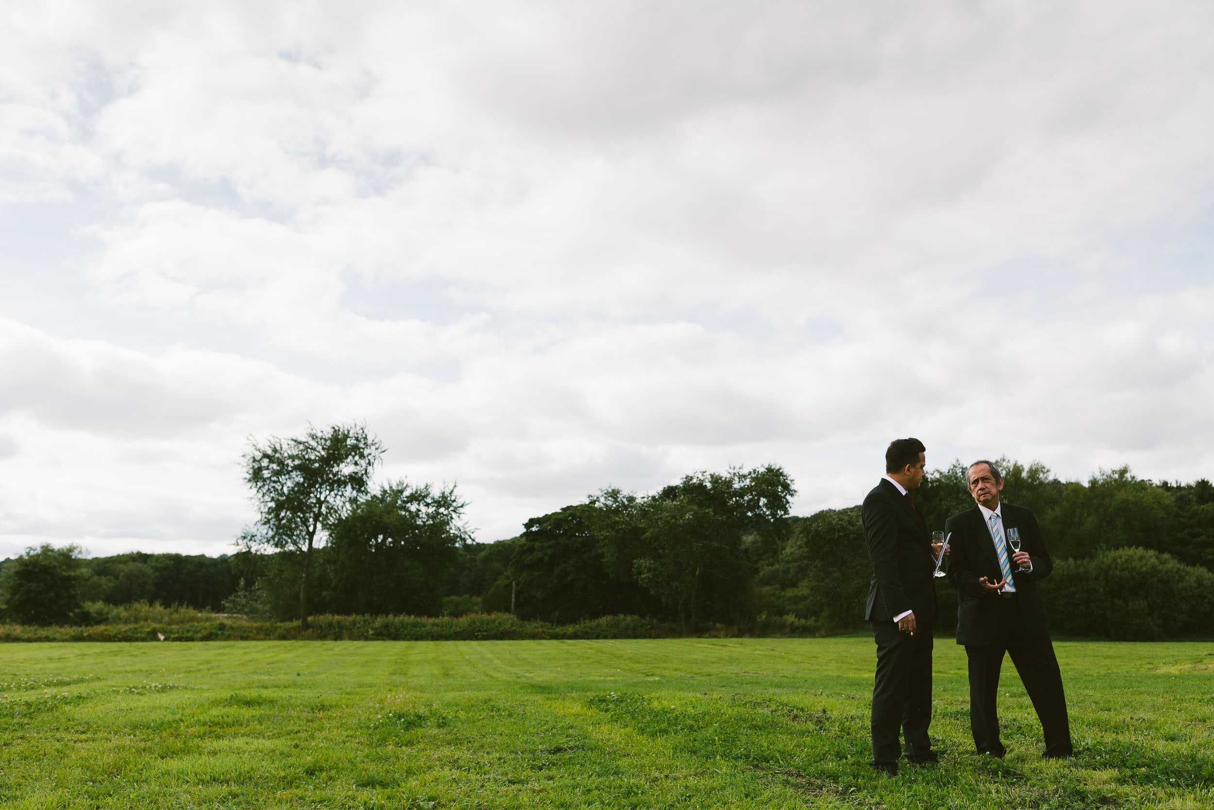 Father of the bride chats with guest in green field during wedding reception