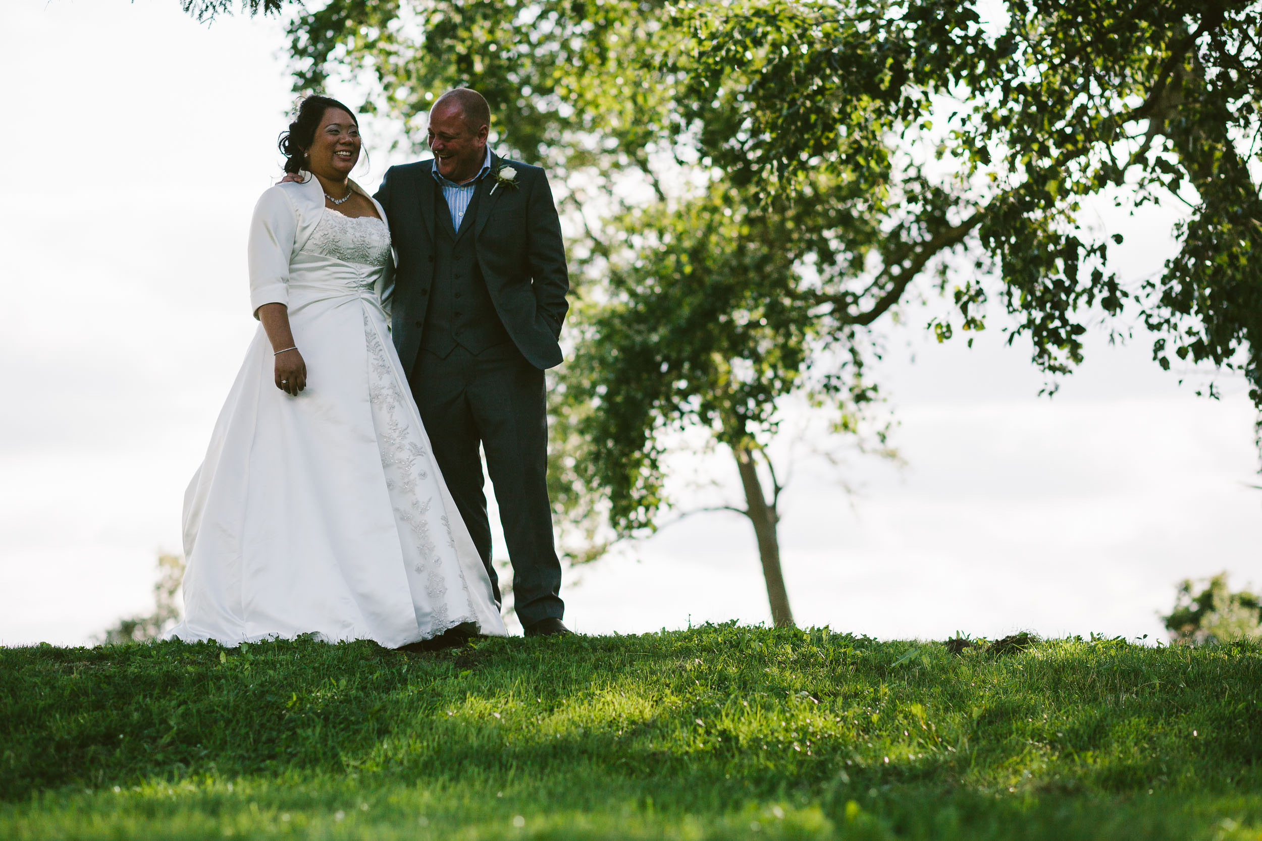 Bride and groom laugh while walking outdoors