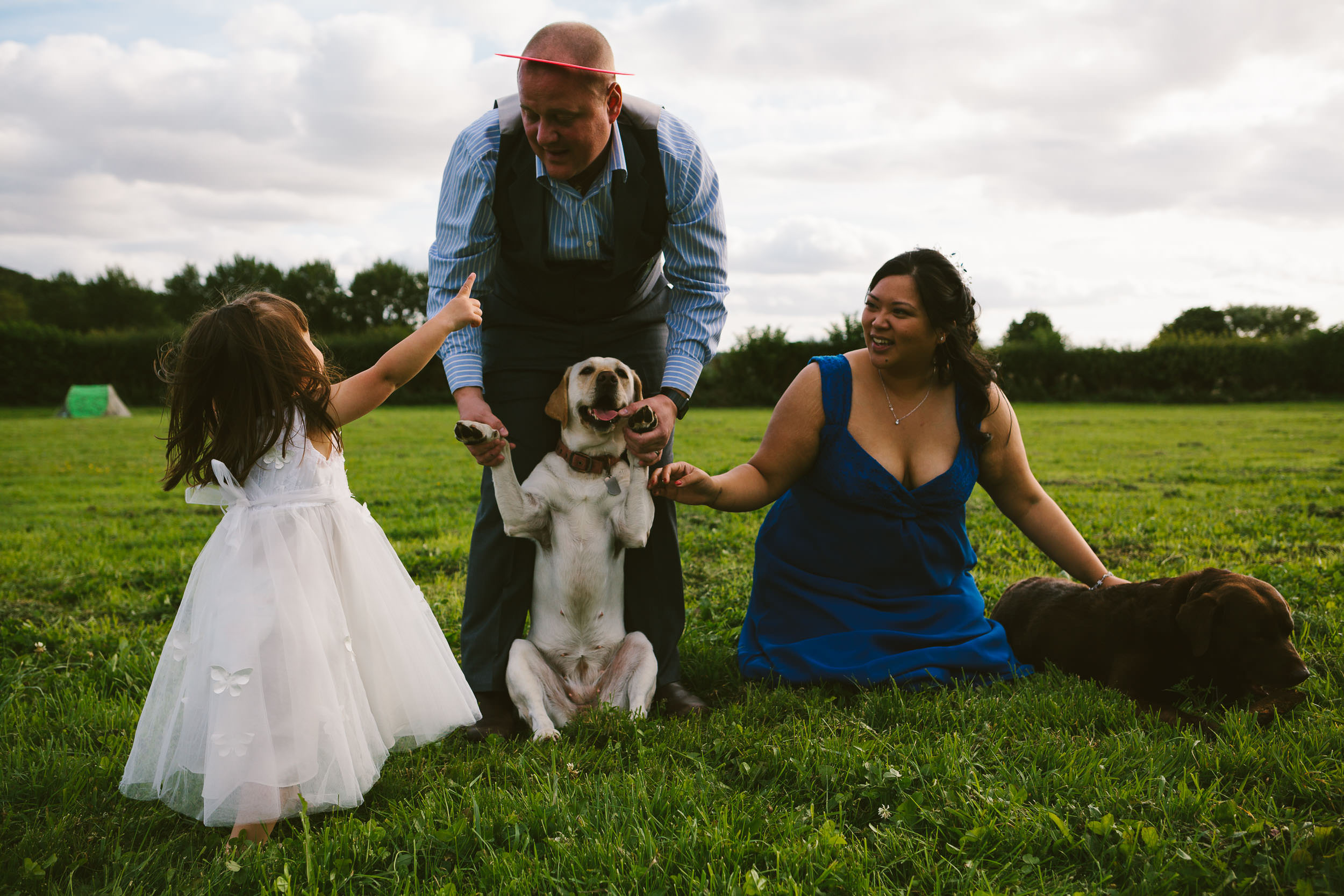 Groom and bridesmaid play with child and dog