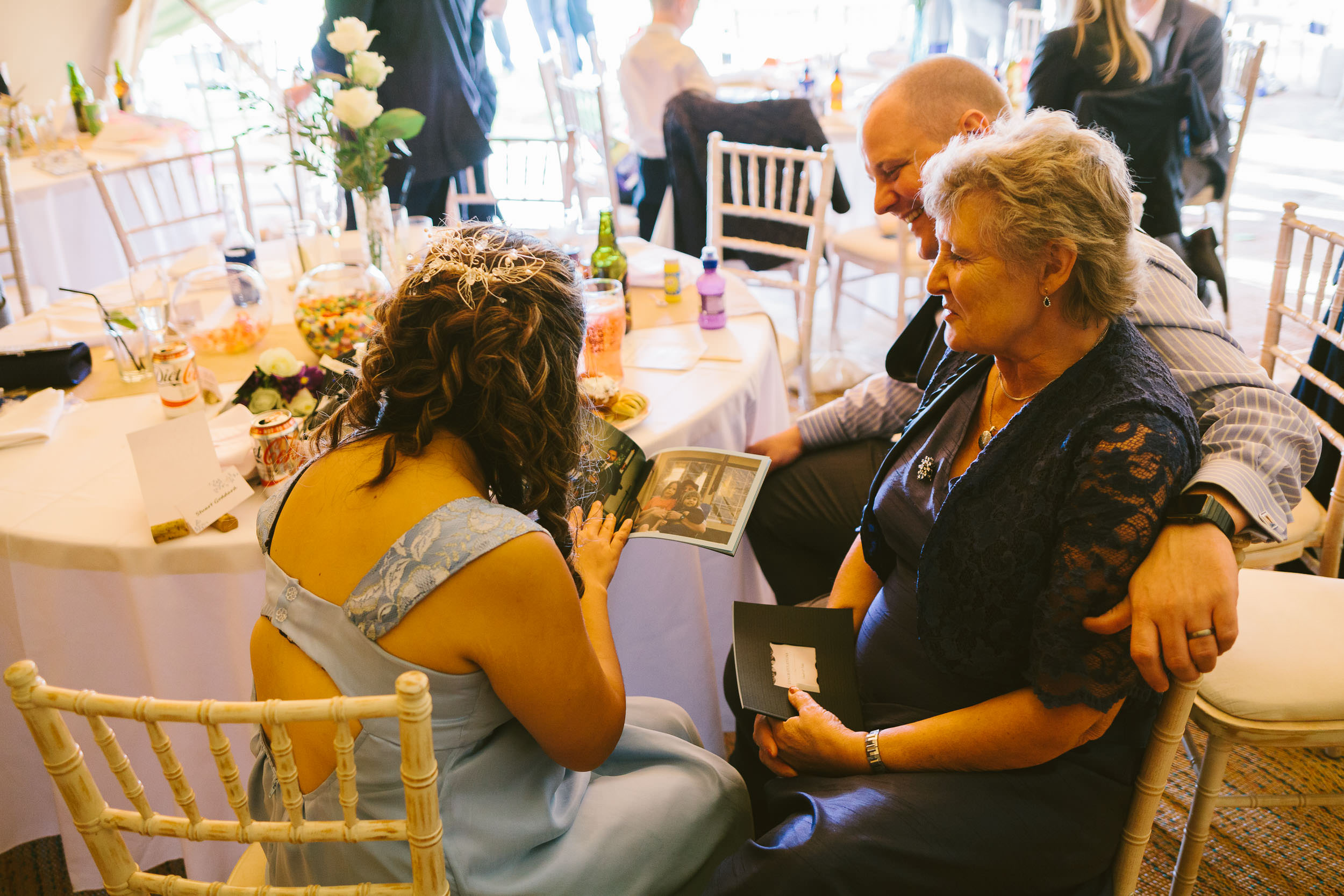 Groom looks through old photo album with his mother
