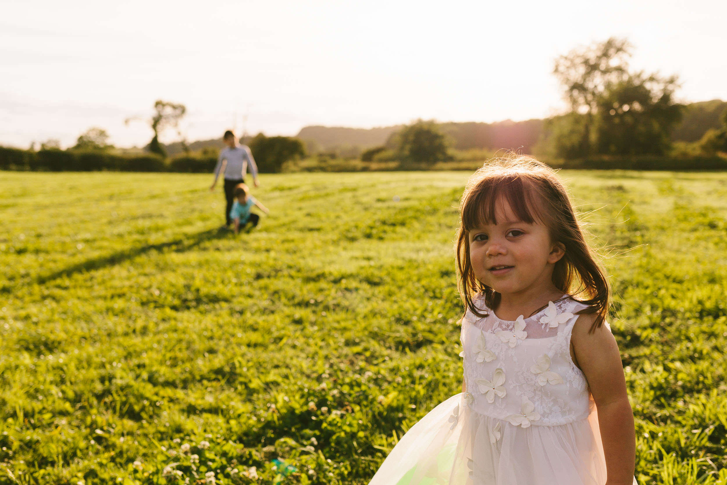 Bride and grooms daughter plays in fields under warm sunlight