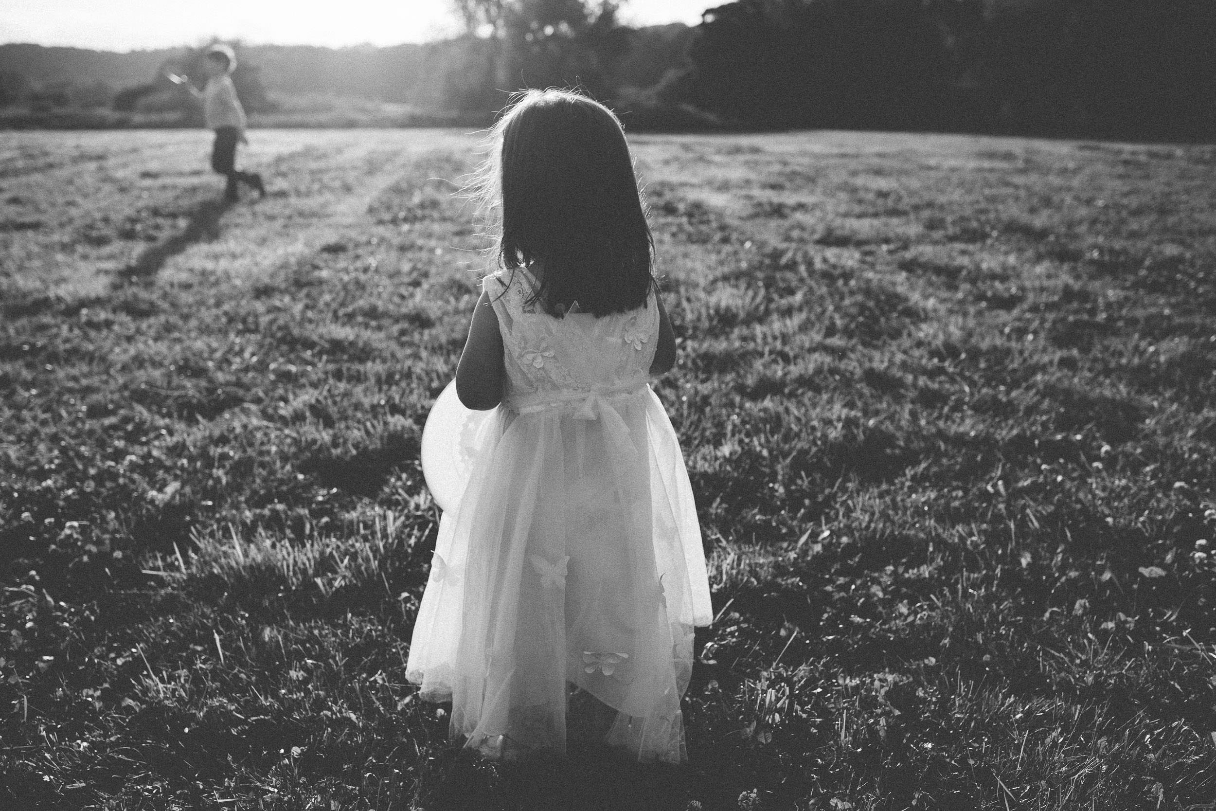 Black and white photo of bride and groom's daughter looking at the setting sun