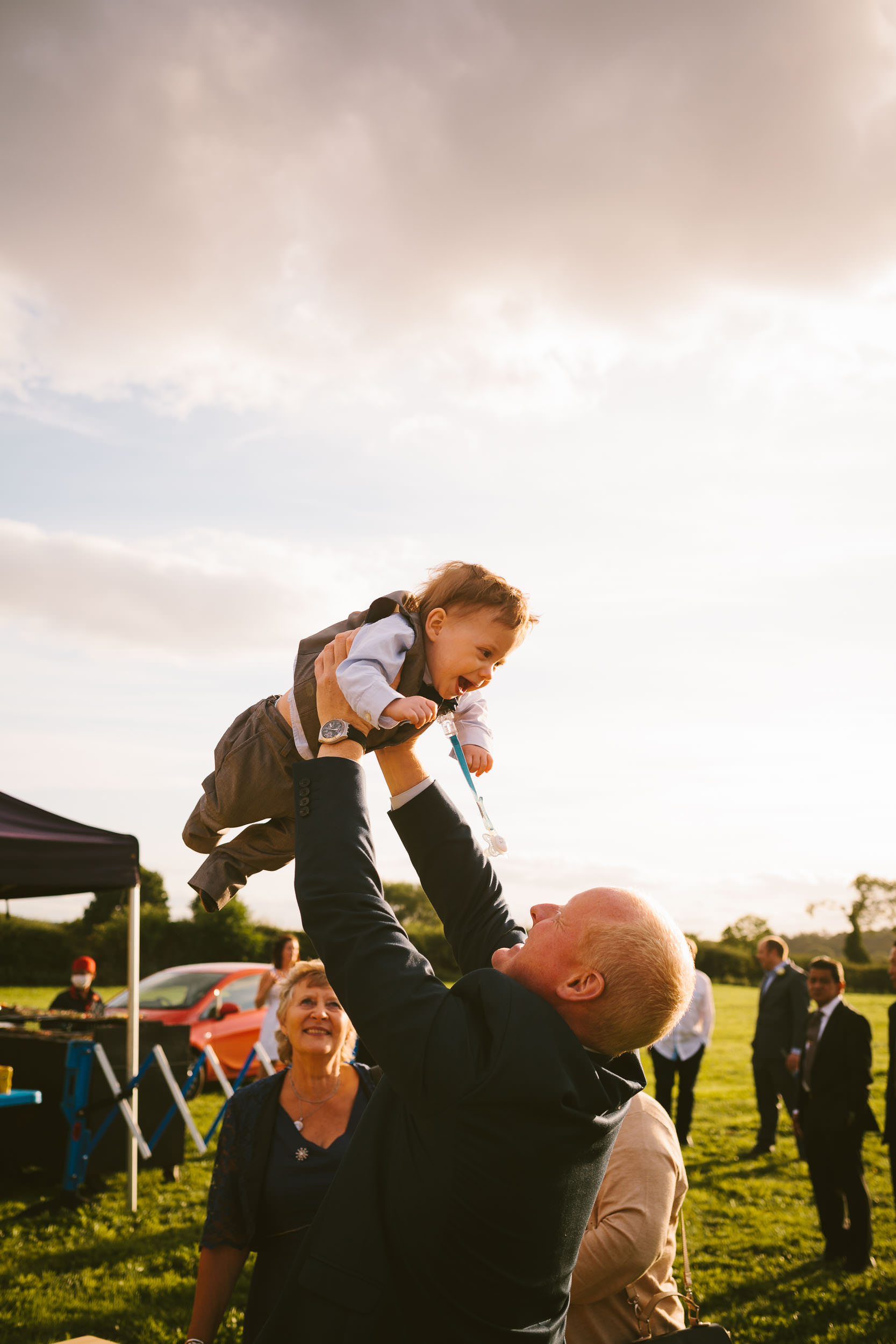 Wedding guest throws laughing baby in the air
