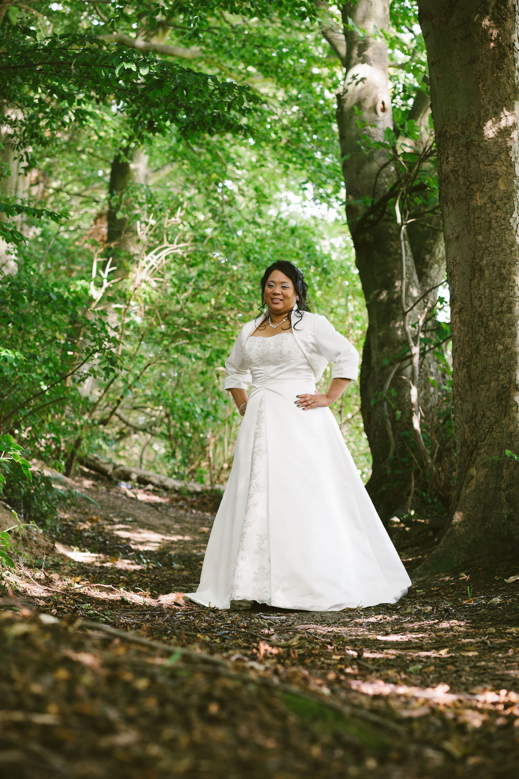 Bride poses on woodland path in dappled light