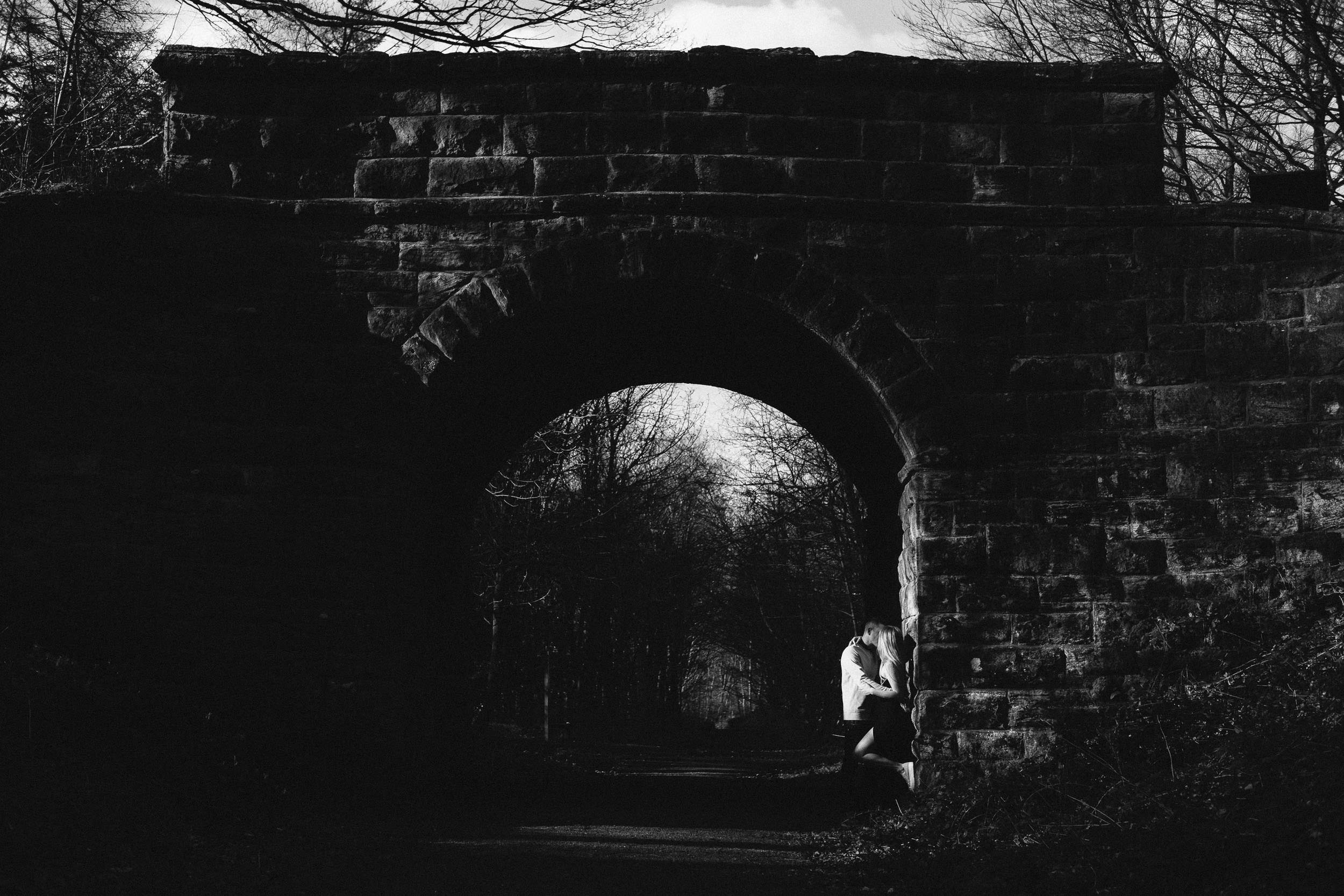 A black and white photo of an engaged couple kissing underneath a railway arch