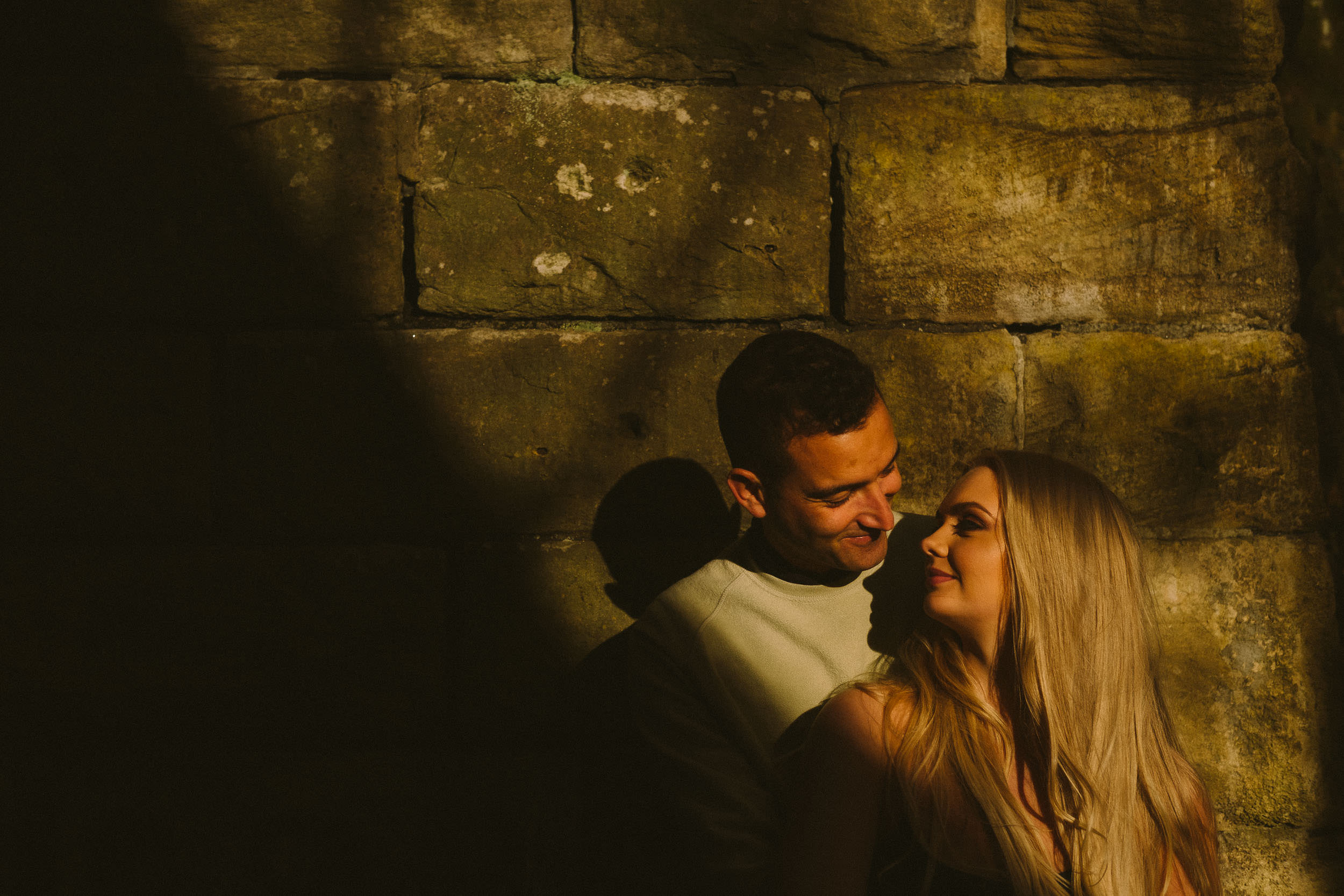 A close up of a couple smiling at each other while leaning against a wall