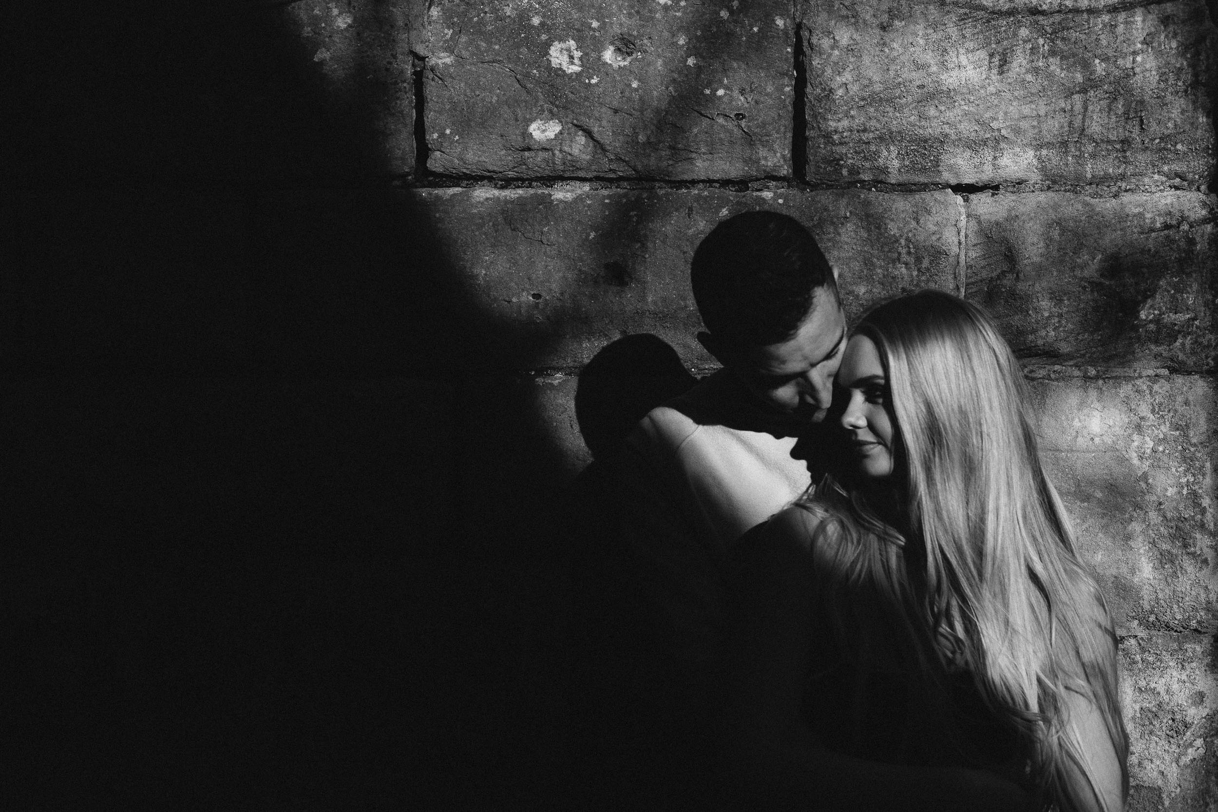 A black and white photo of an engaged couple nuzzling against a wall with deep shadow all around