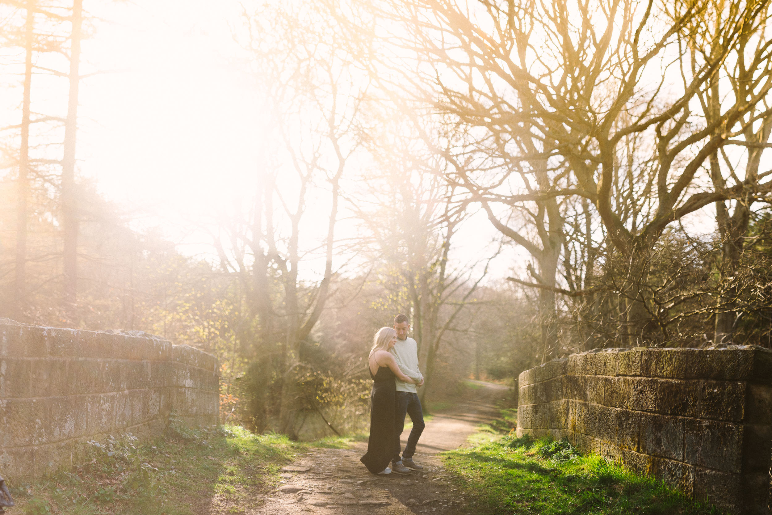 A couple embracing on a bridge with strong sunshine coming through the trees