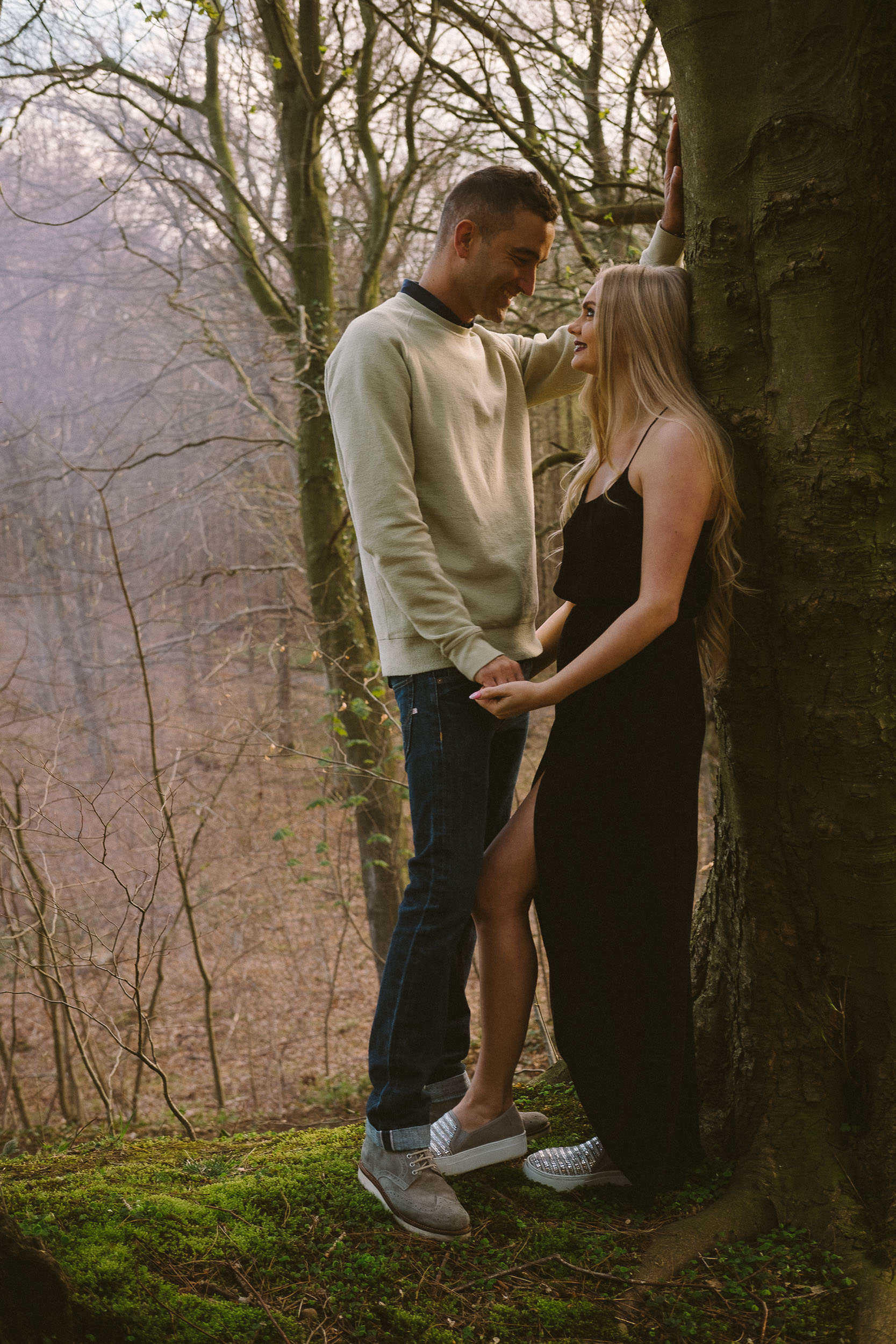 A couple hold hands and tenderly look into each other's eyes while leaning against a tree