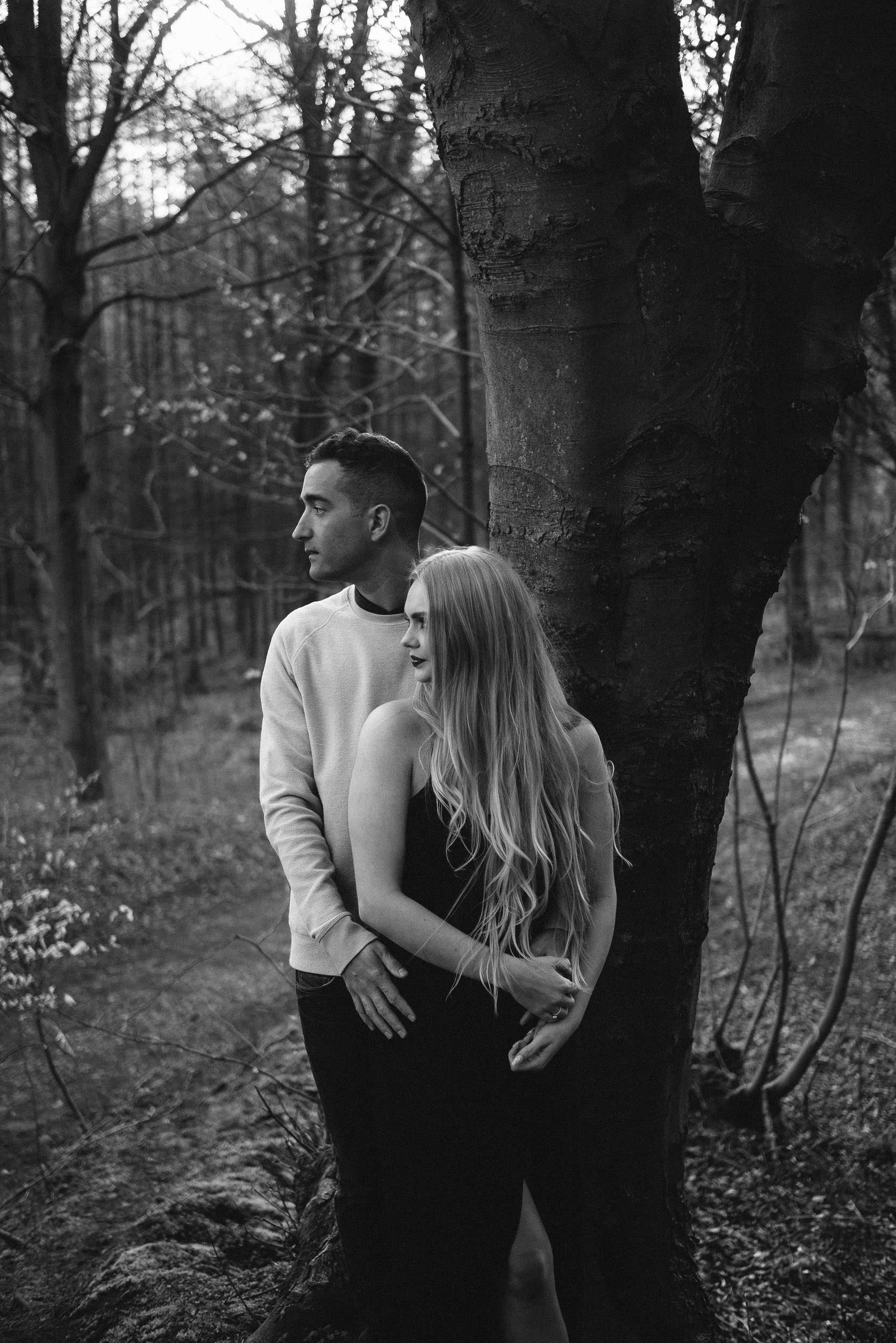 A black and white photo of an engaged couple looking to the side while standing near a tree
