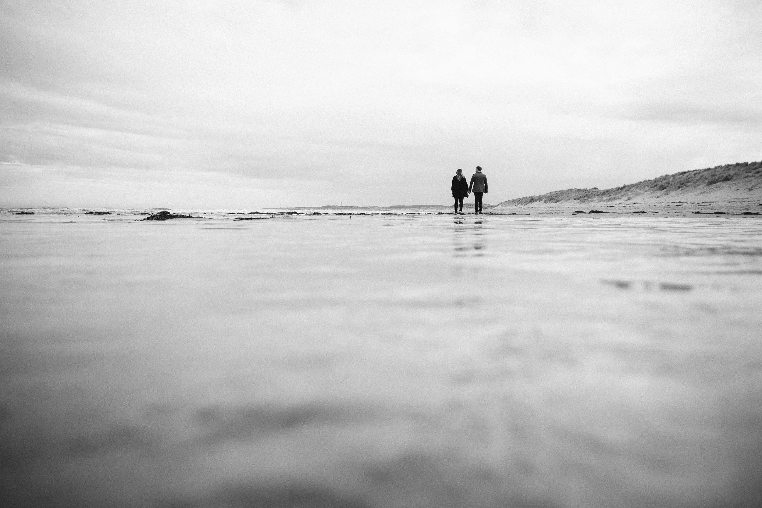 A black and white photo of a couple in the distance walking hand in hand on a beach