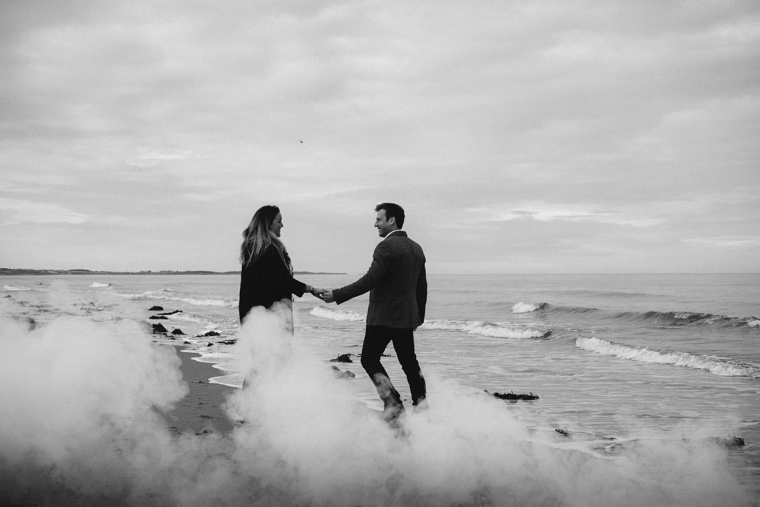 A black and white photo of an engaged couple holding hands on a beach surrounded by smoke