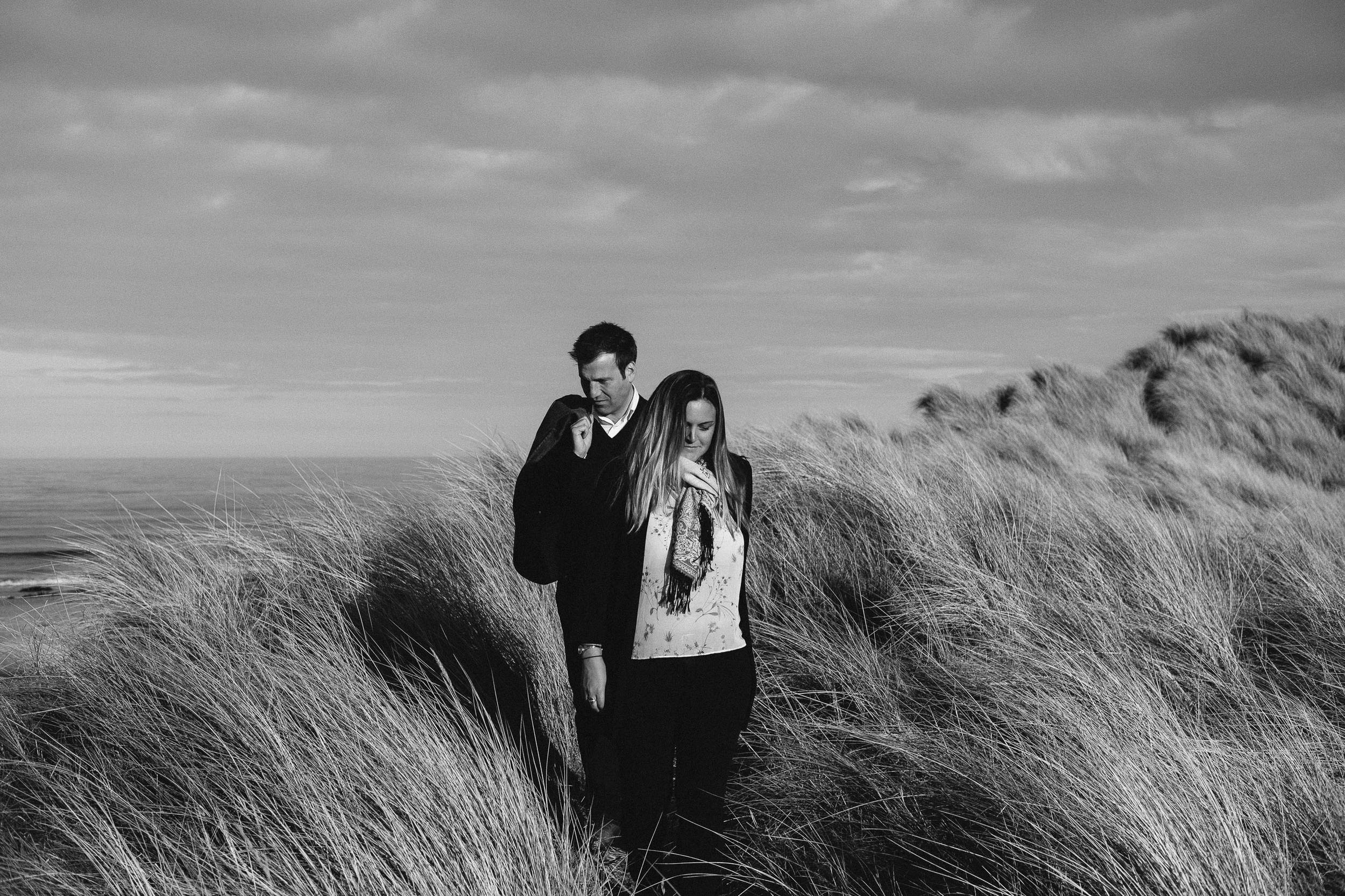 A black and white photo of an engaged couple walking through long grass on sand dunes