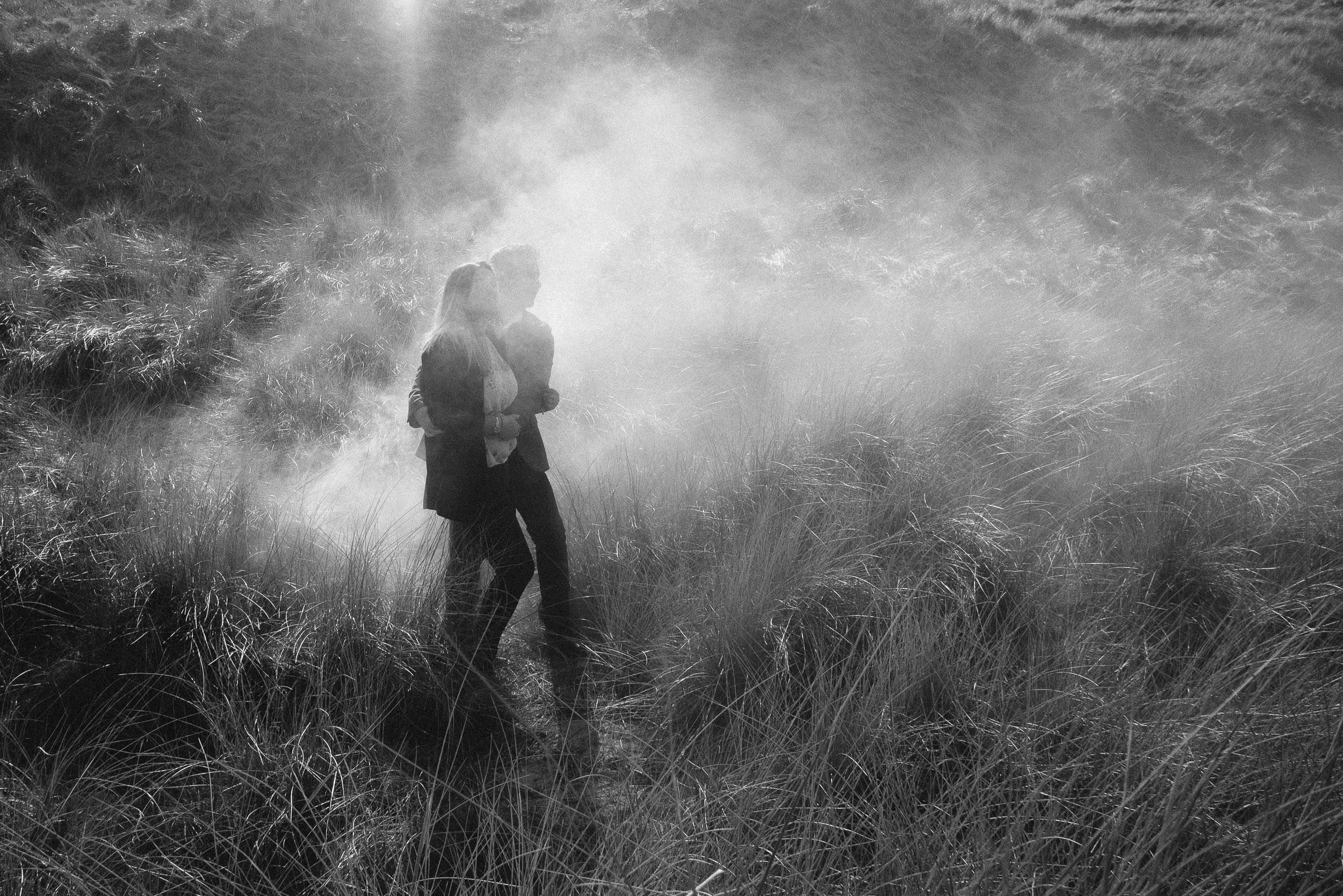 A black and white photo of an engaged couple cuddling while surrounded by smoke and long grass
