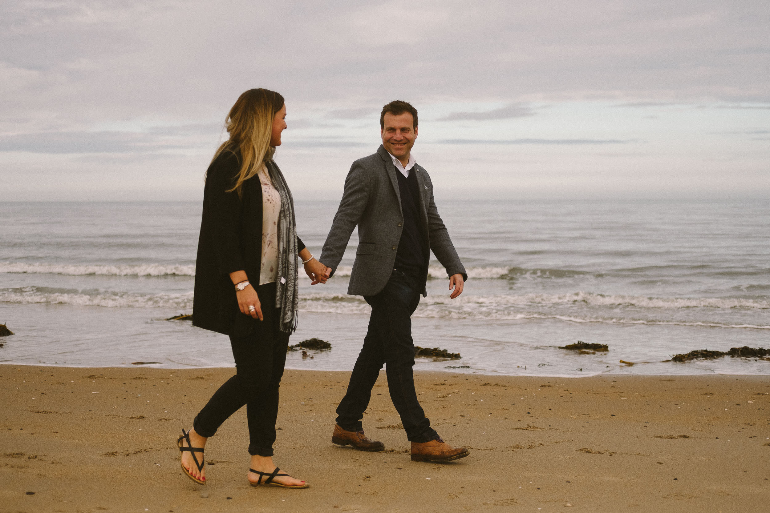 A couple walking on a beach holding hands and smiling at each other