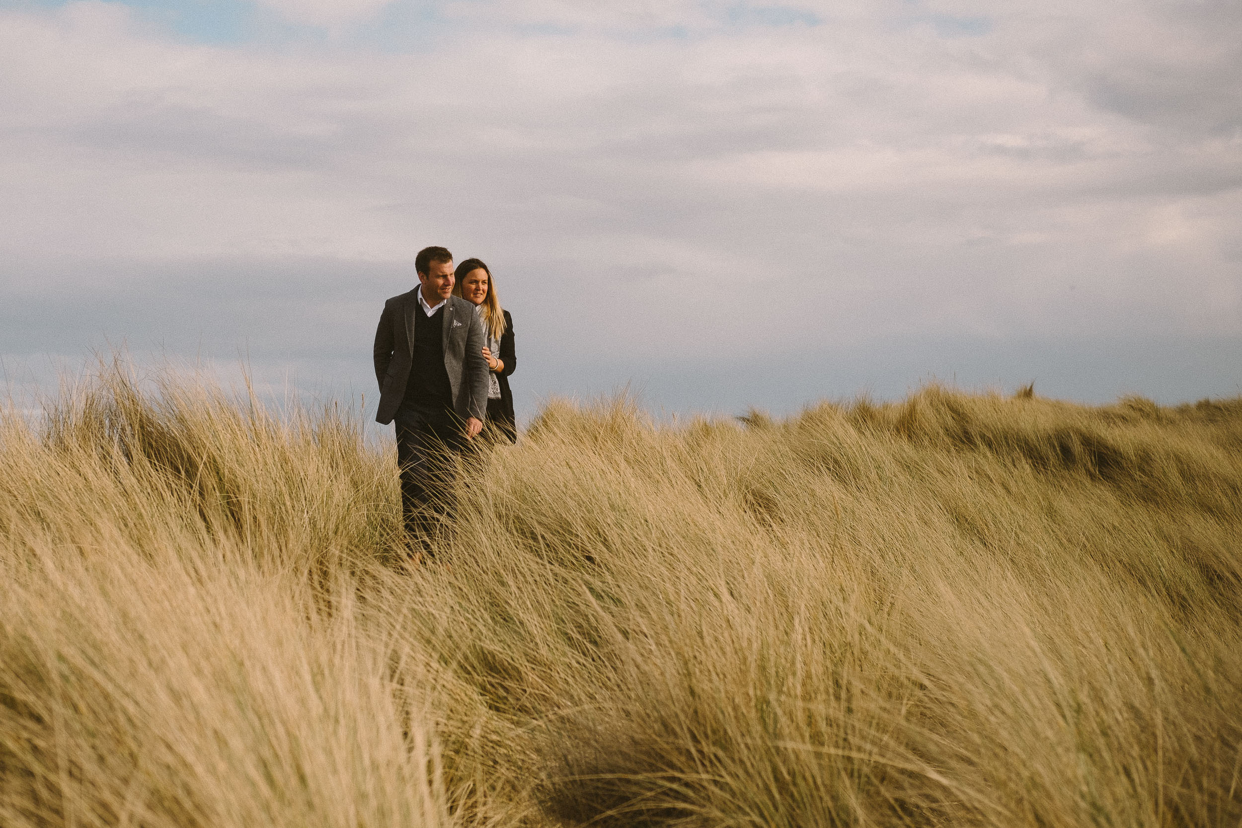 A couple cuddle while standing on grass covered sand dunes in Northumberland