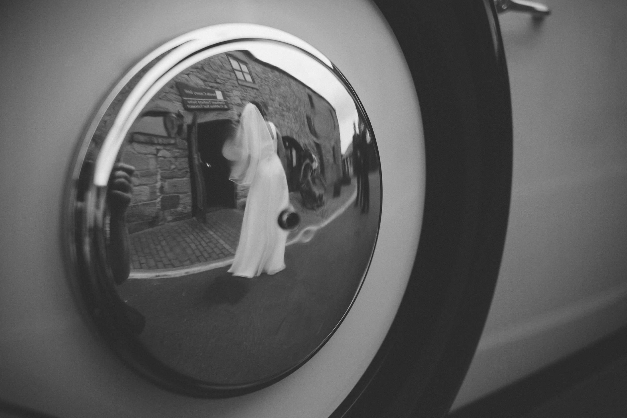 Black and white photo of the bride reflected in the hubcap of the wedding car