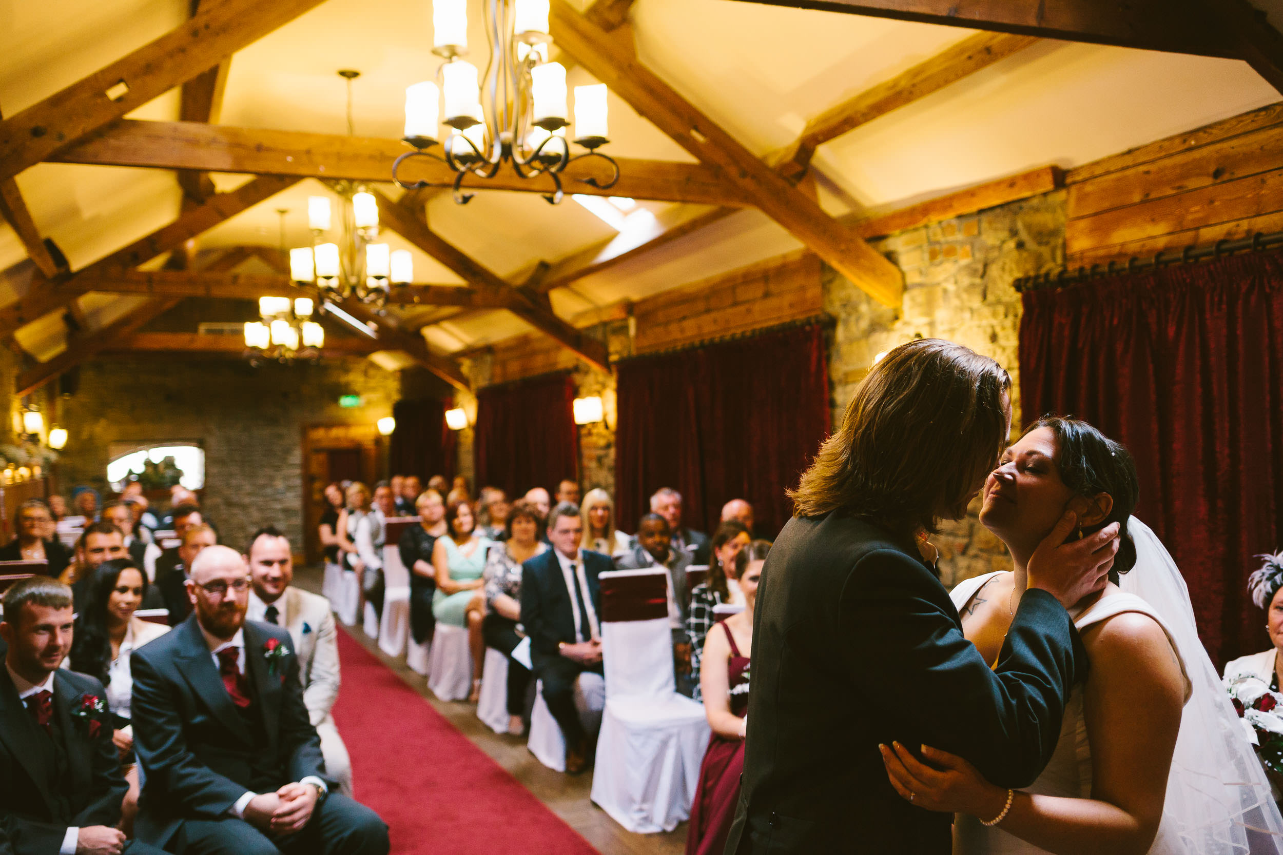 Bride and groom kiss during wedding ceremony with guests watching