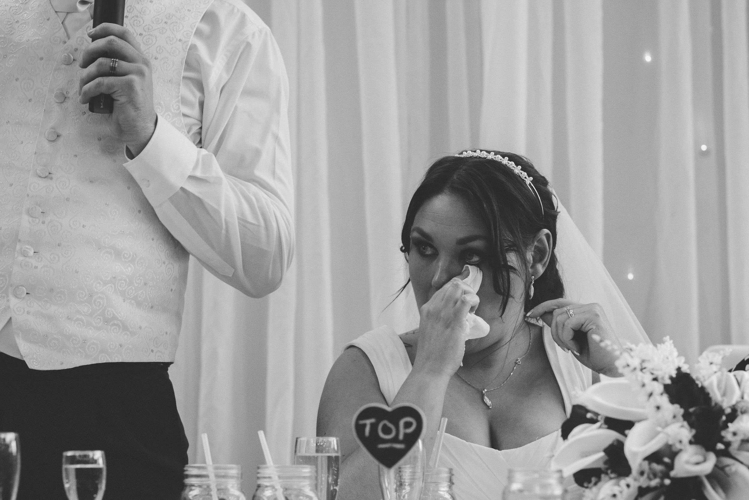 Black and white photo of bride crying during speeches