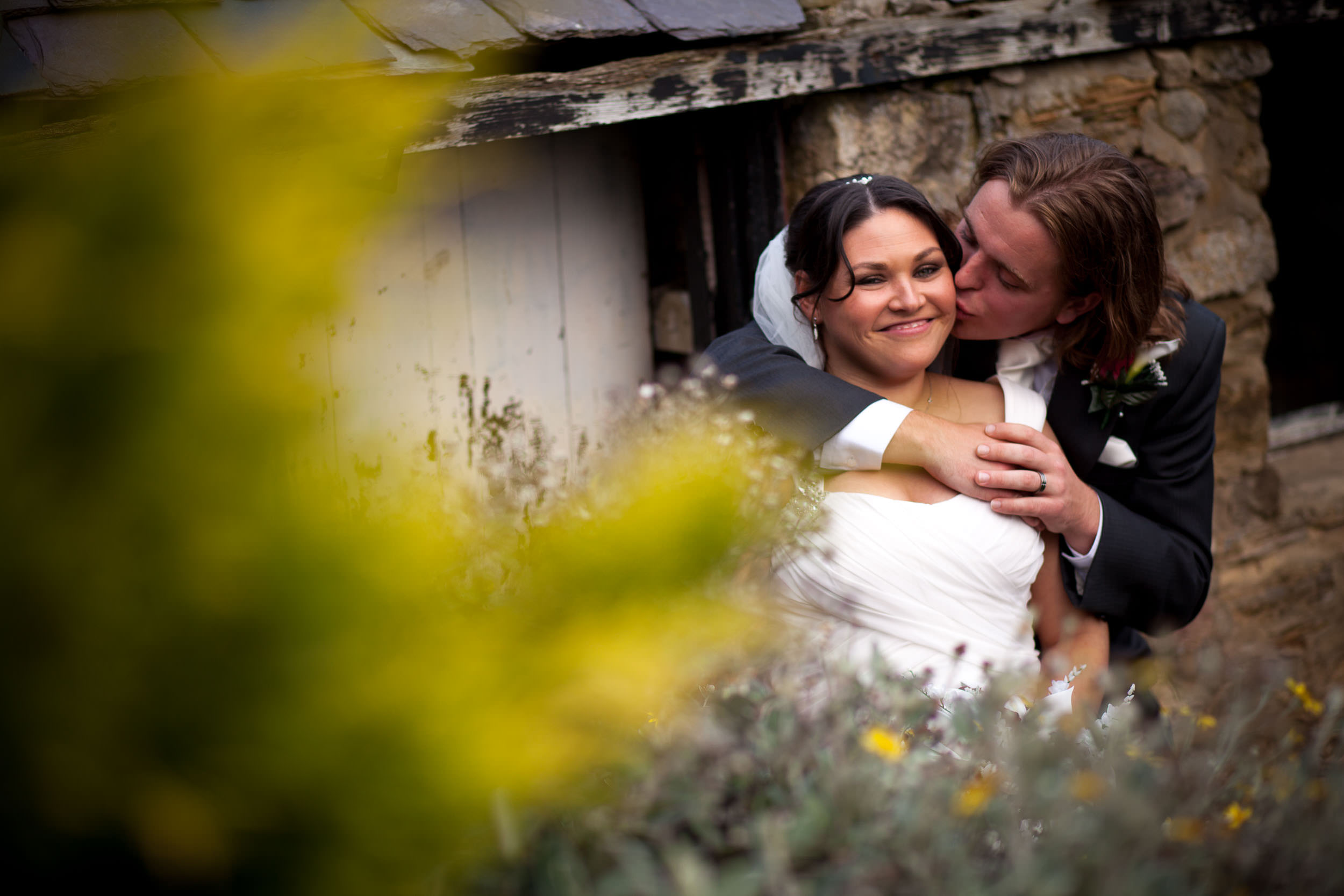 Bride and groom kiss with flowers in foreground