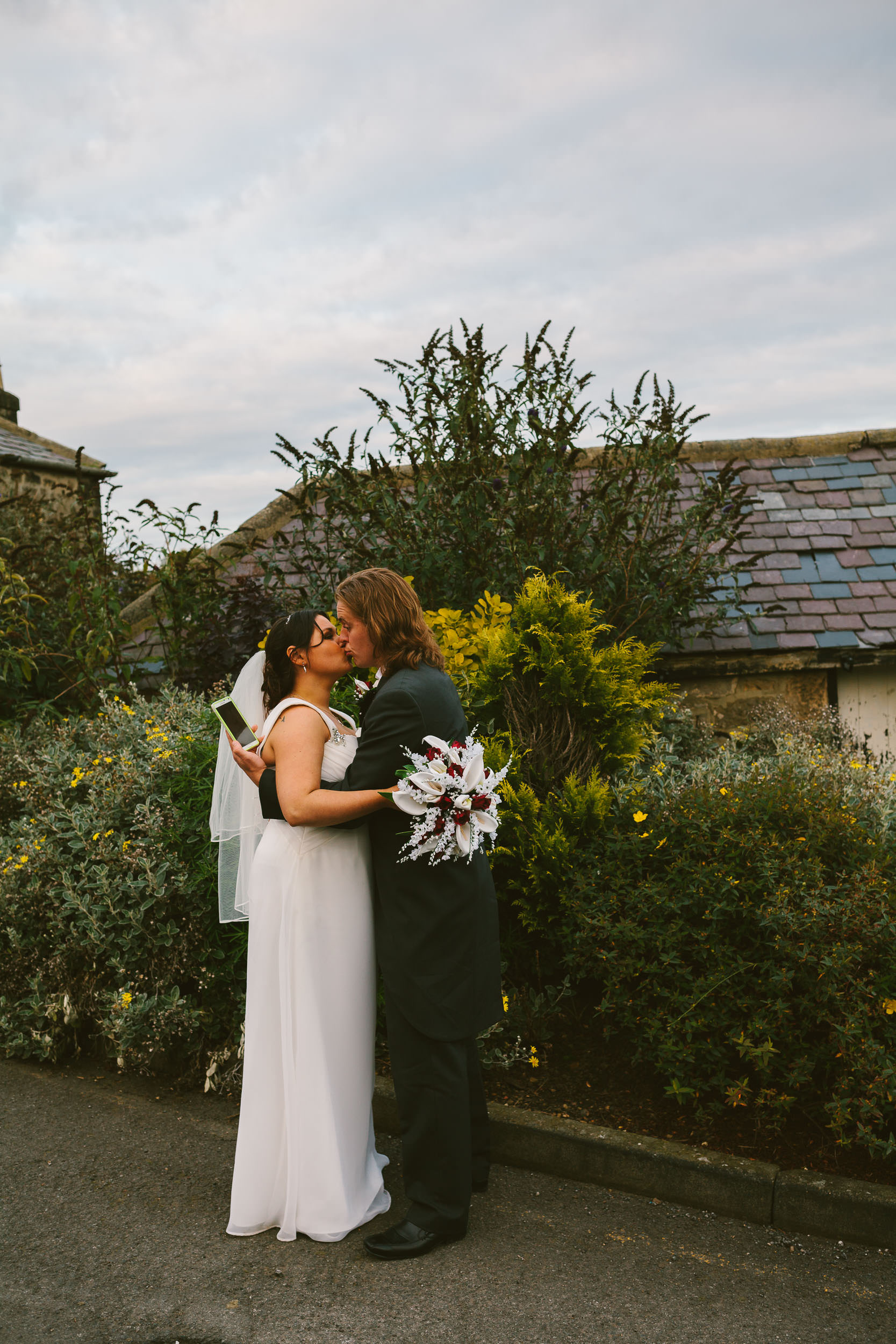 Groom looks at phone while kissing bride