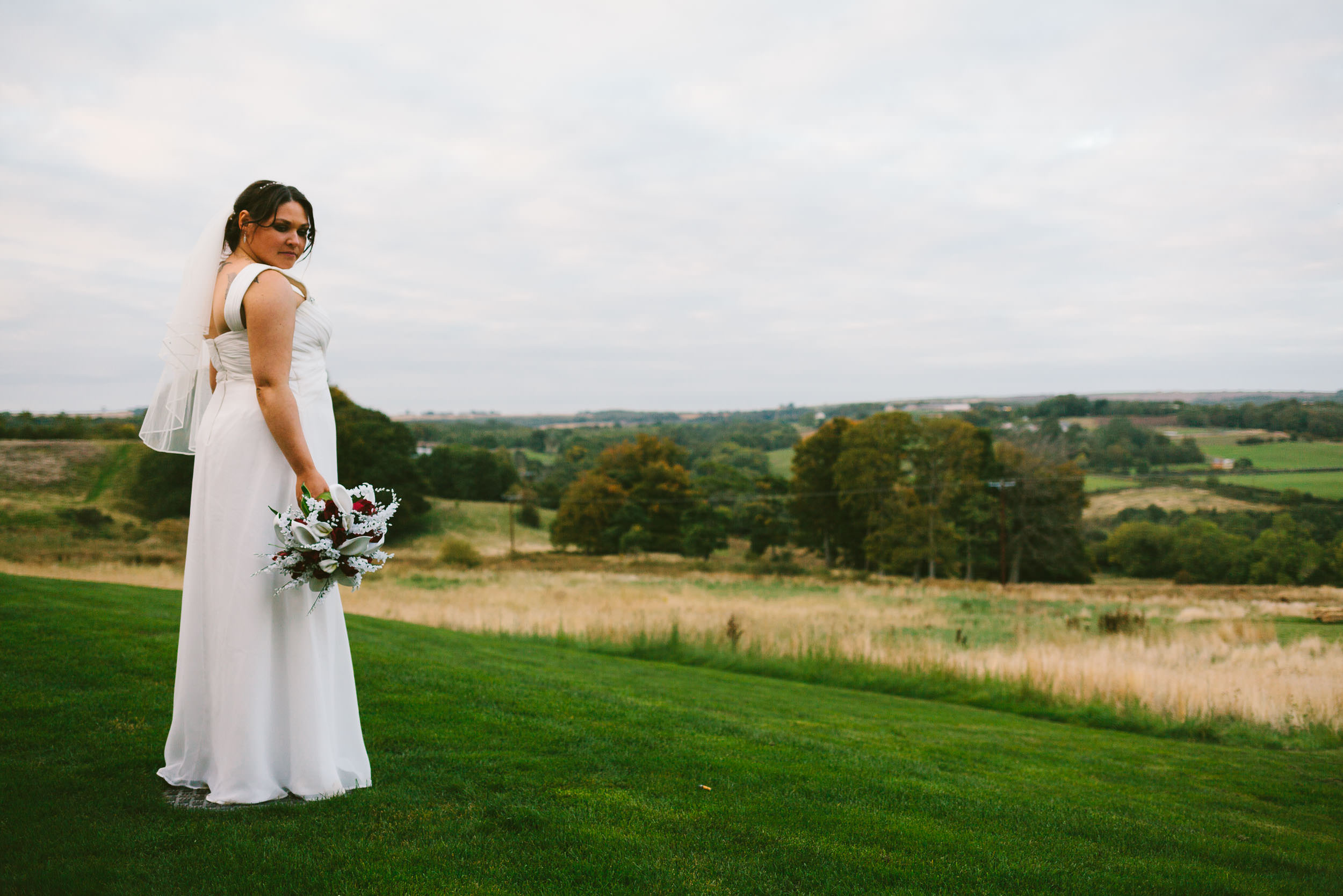 Bride poses with flowers in front of green valley
