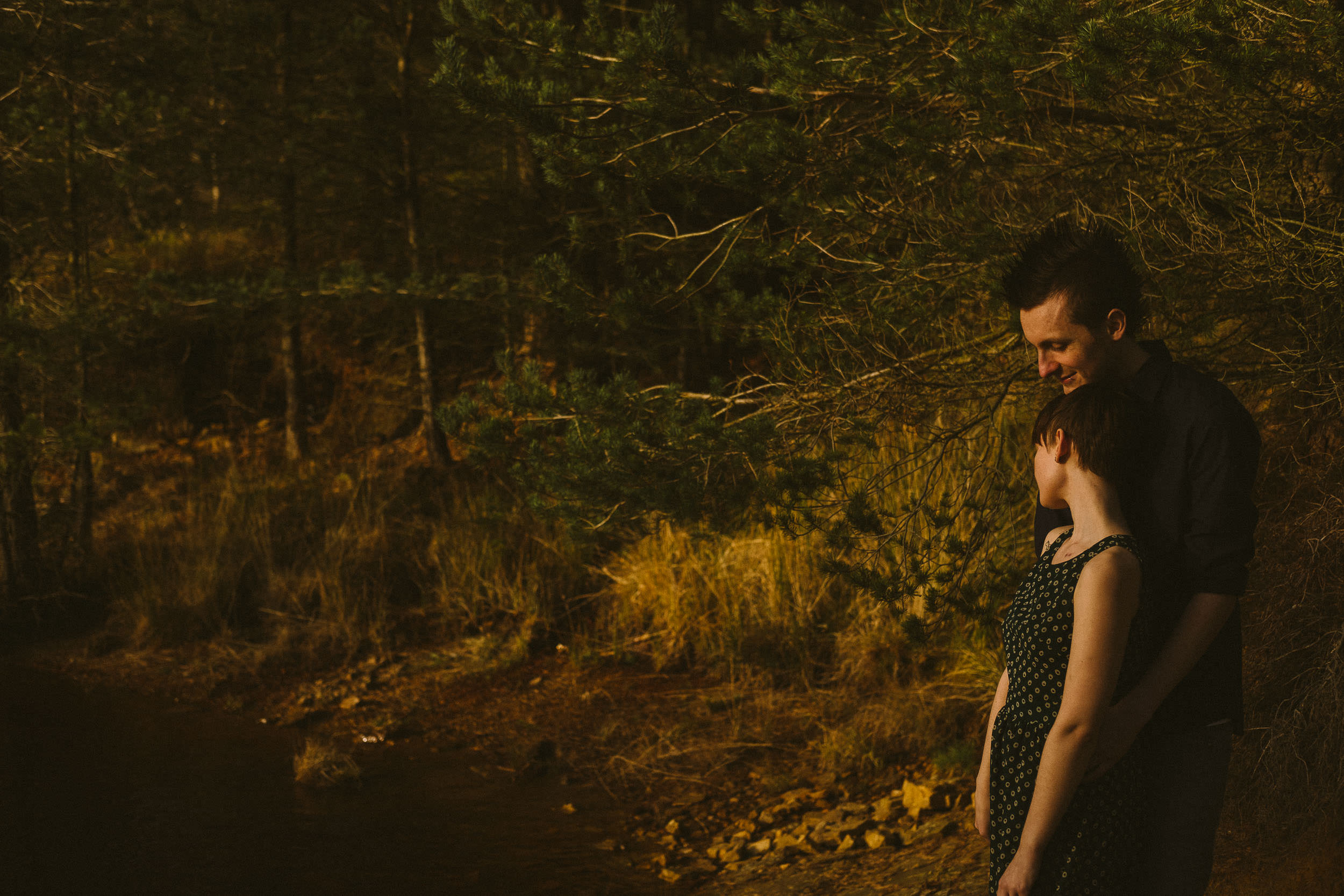 Romantic photo of girl leaning against guy with trees in the background